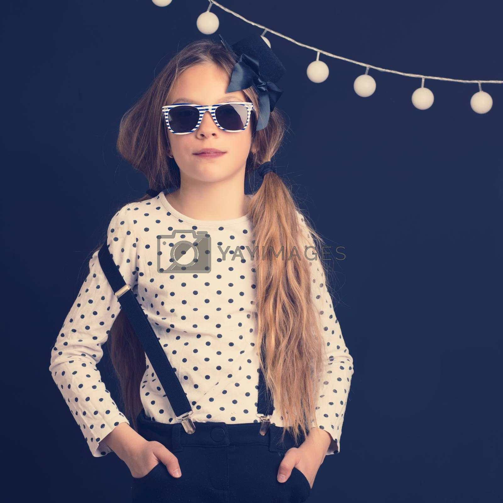 Fashion photo of young hipster child wearing cool clothes and sunglasses standing over dark wall, instagram toned image