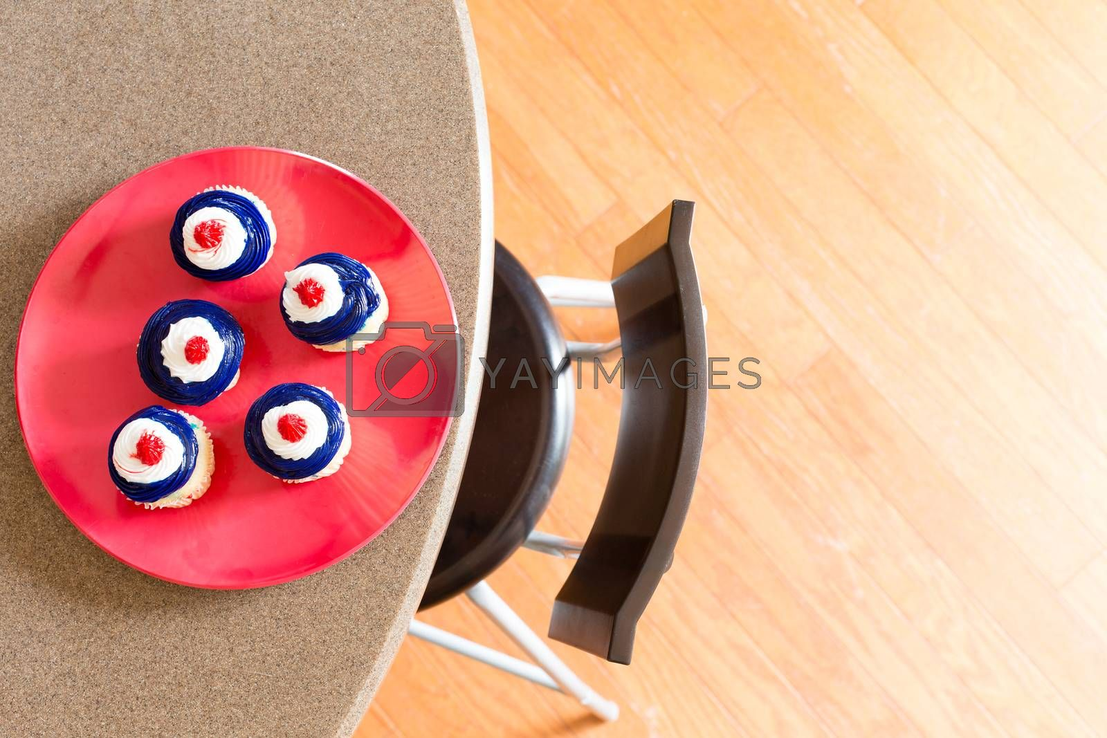 Patriotic 4th July Independence Day cupcakes with red, white and blue icing served on a red plate on a table, overhead view with copyspace on a wooden parquet floor