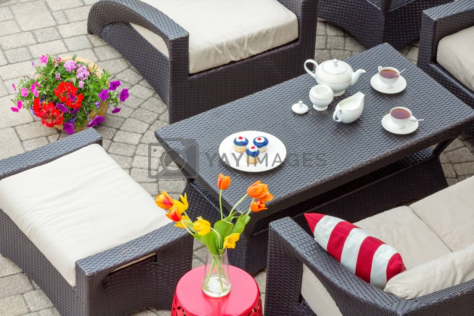 4th July tea served on an outdoor patio with patriotic cupcakes and cups of tea on a table surrounded by comfortable armchairs and a stool with spring tulips in a vase