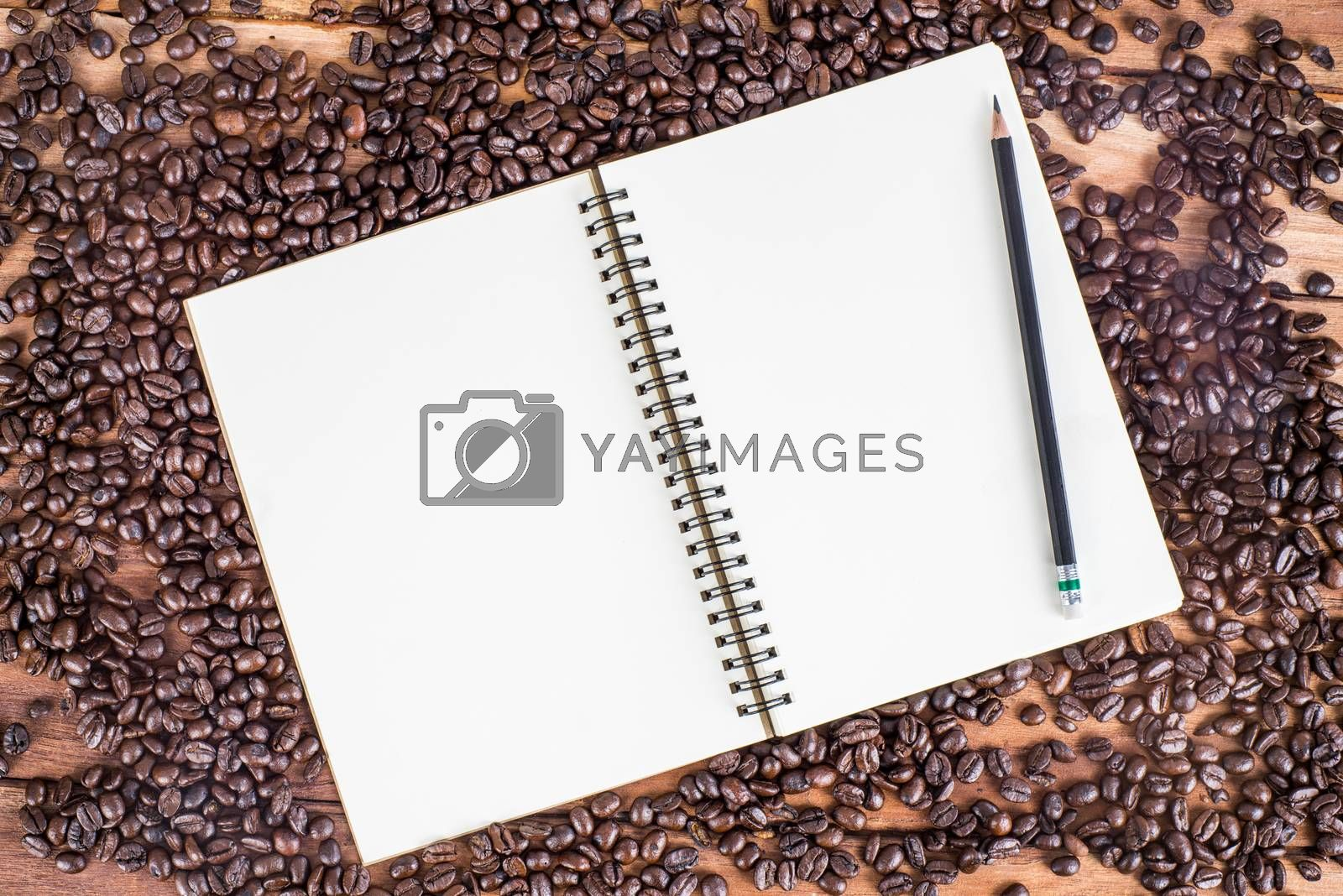 Royalty free image of Pencil, notebook, coffee bean on wooden background by iamway