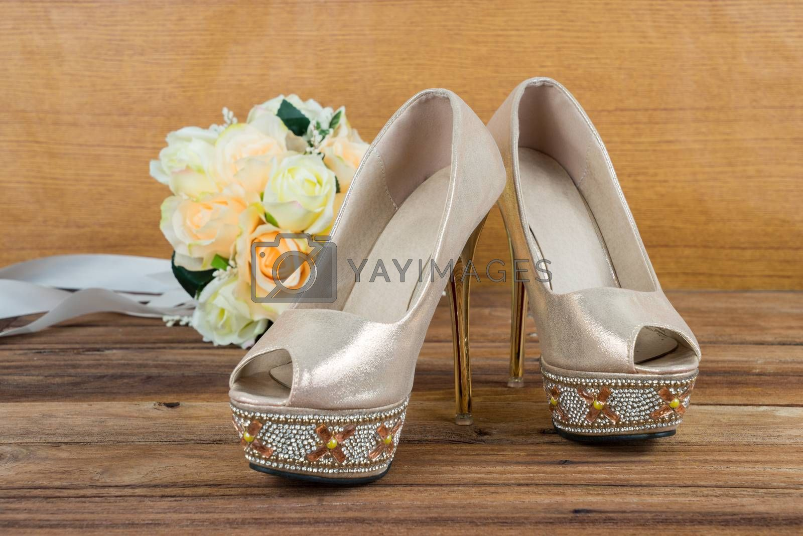 Royalty free image of Wedding bouquet with bride's shoes on wood background by iamway