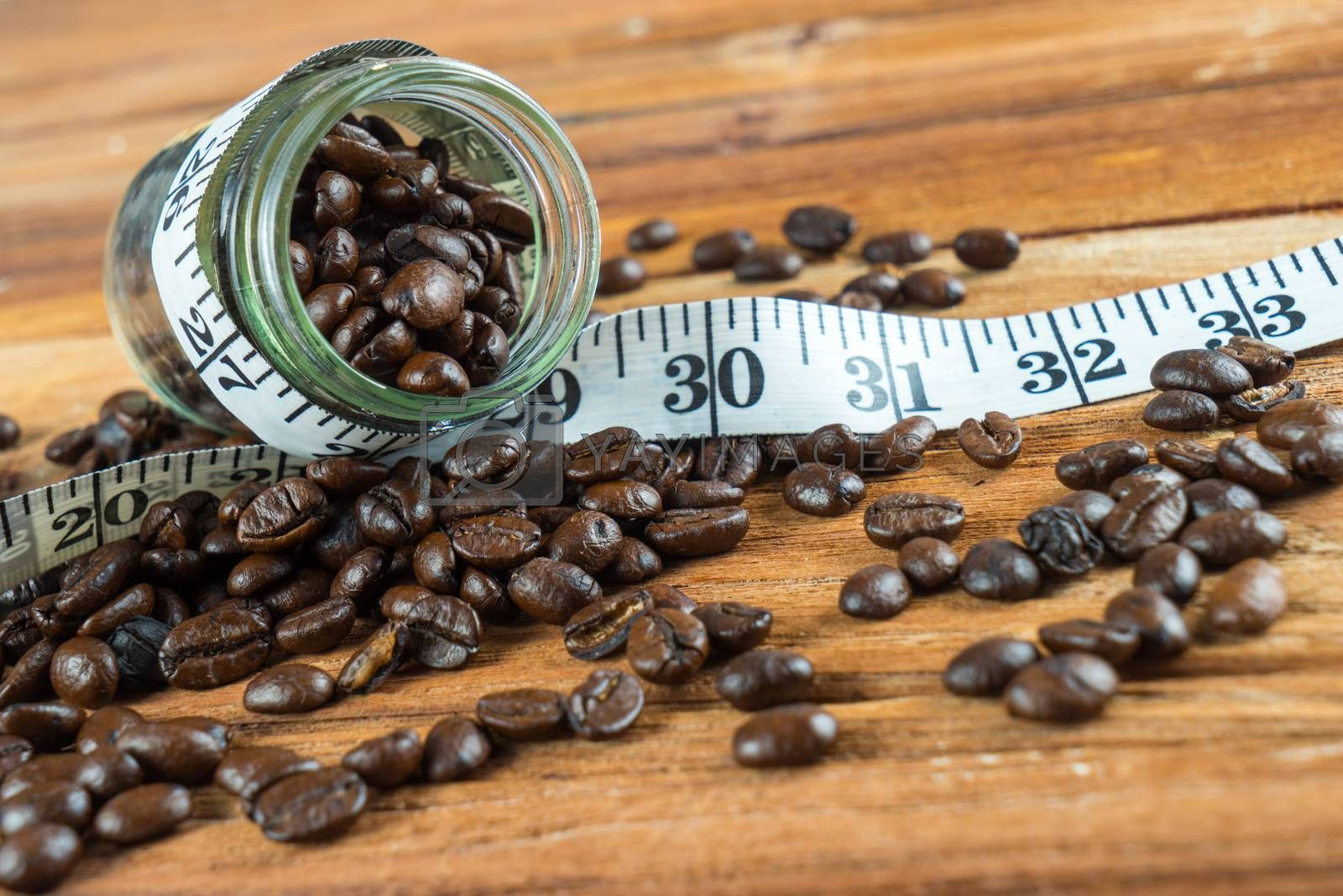 Royalty free image of Coffee bean in glass bottle with tape measure on wooden backgrou by iamway