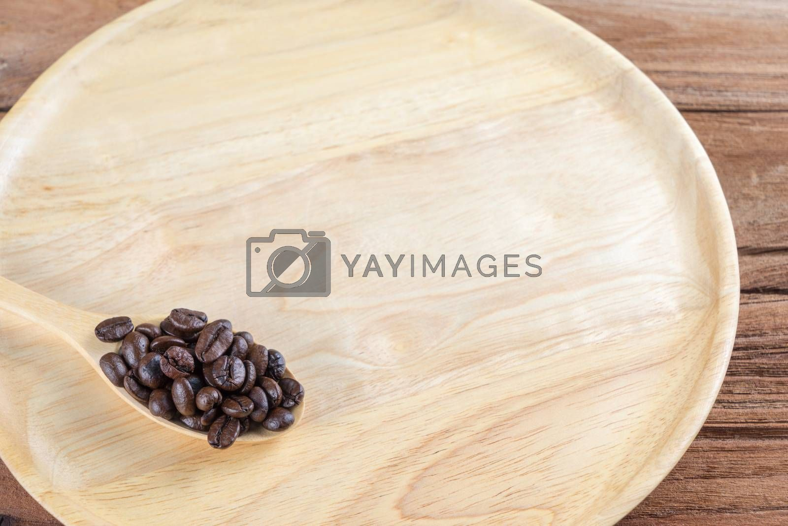 Royalty free image of Coffee bean on wooden spoon, dish, table background by iamway