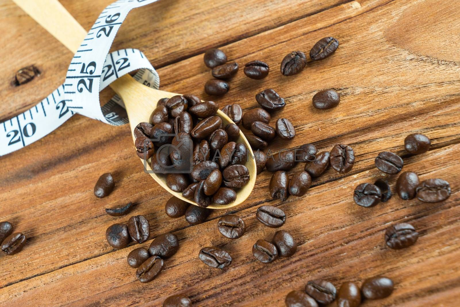 Royalty free image of Coffee bean on wooden spoon, tape measure on wooden background by iamway