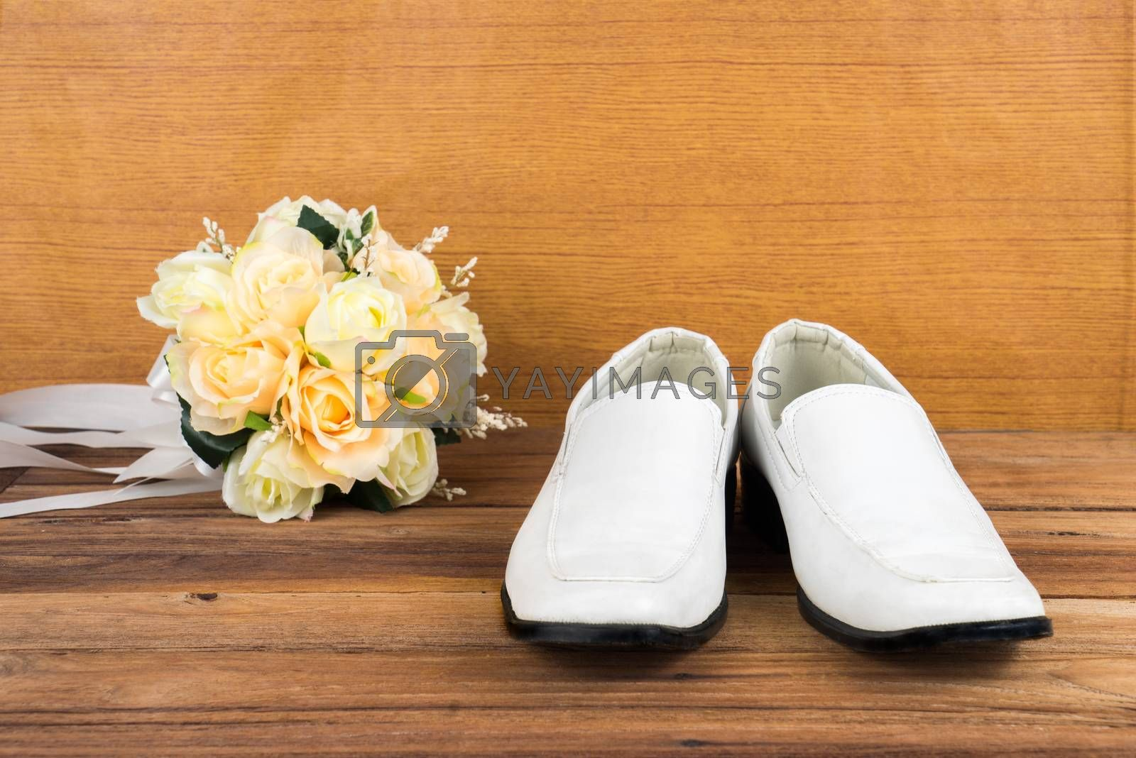 Royalty free image of Wedding bouquet with groom's shoes on wood background by iamway