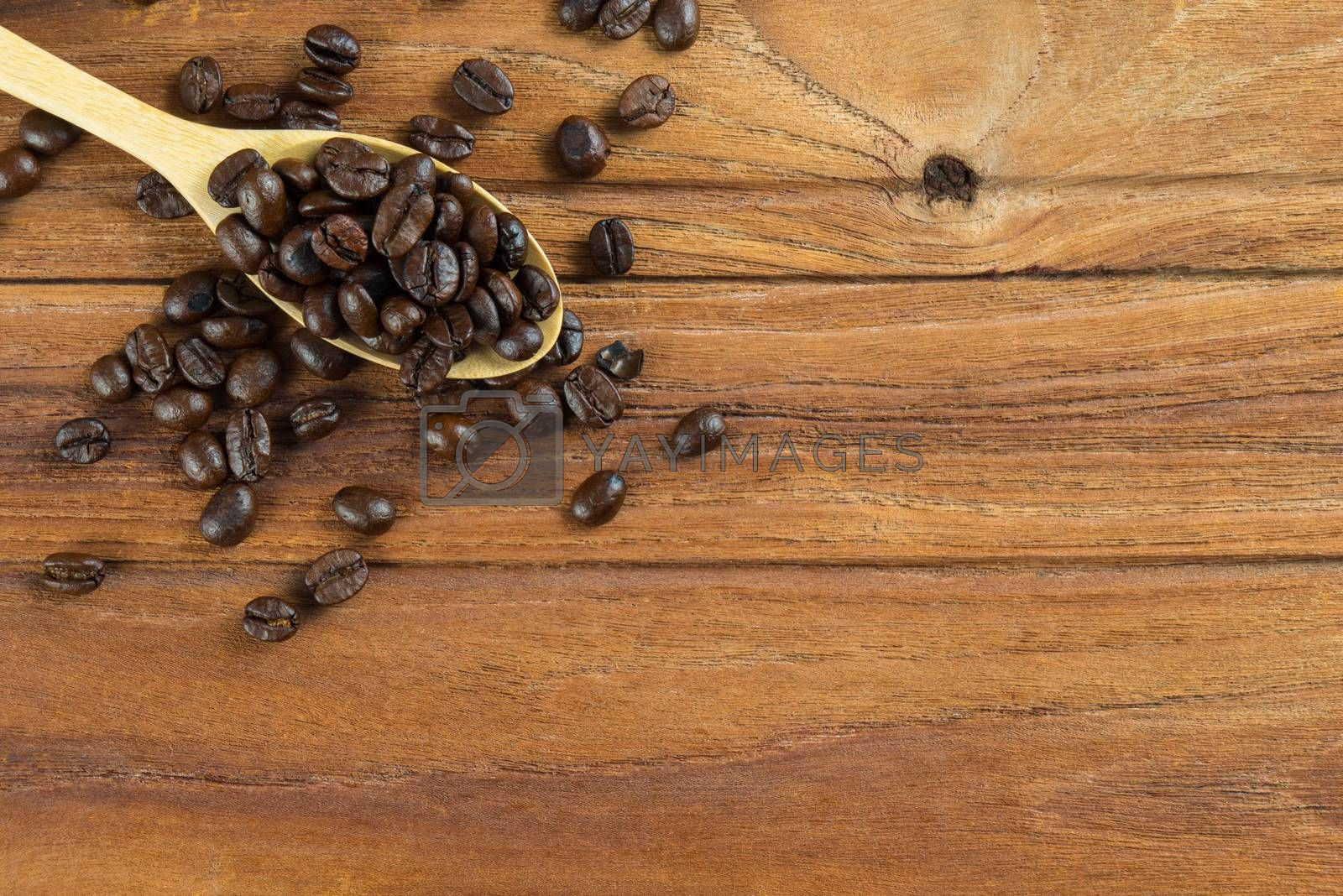 Royalty free image of Coffee bean on wooden spoon, wooden table background by iamway