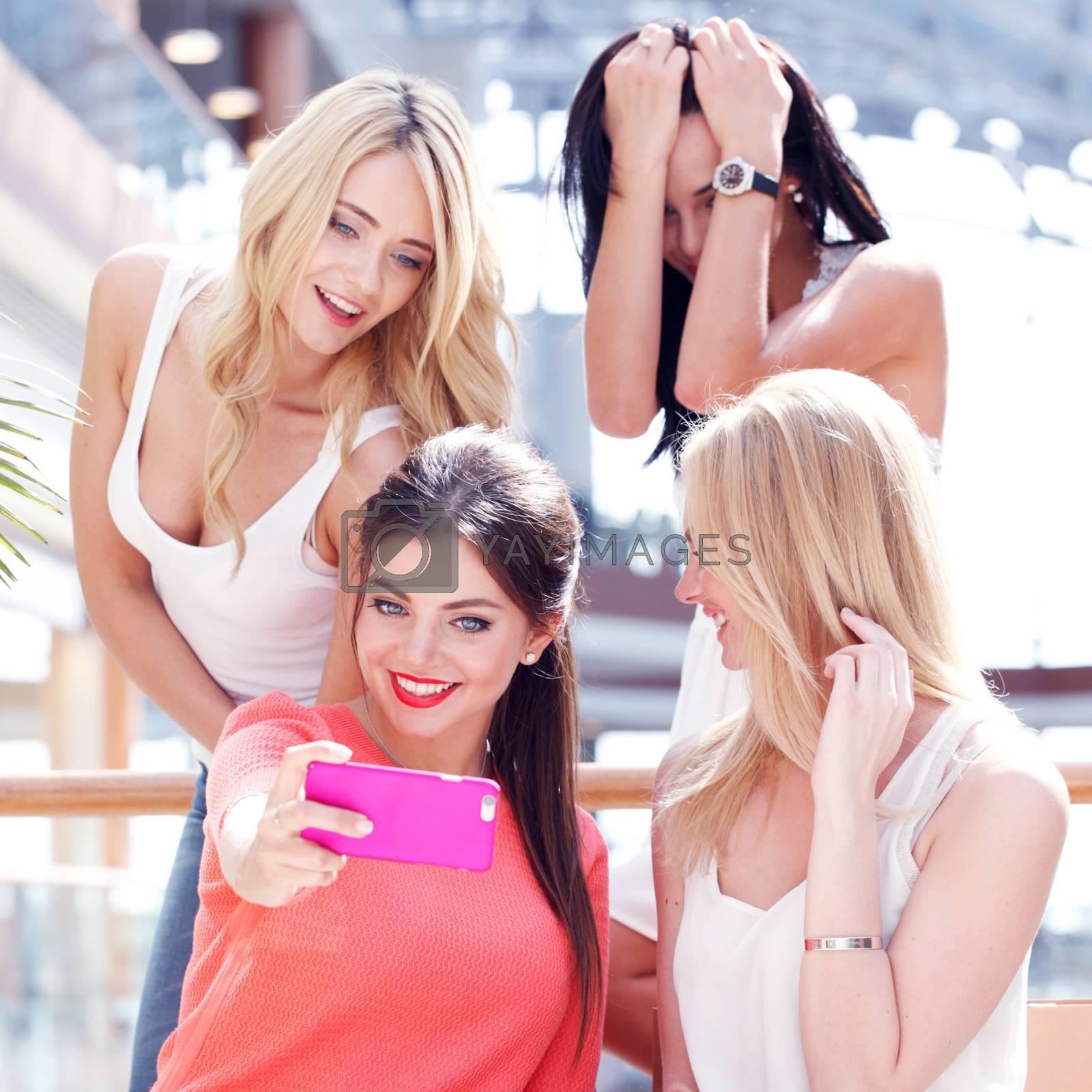 Happy female friends taking selfie in shopping mall