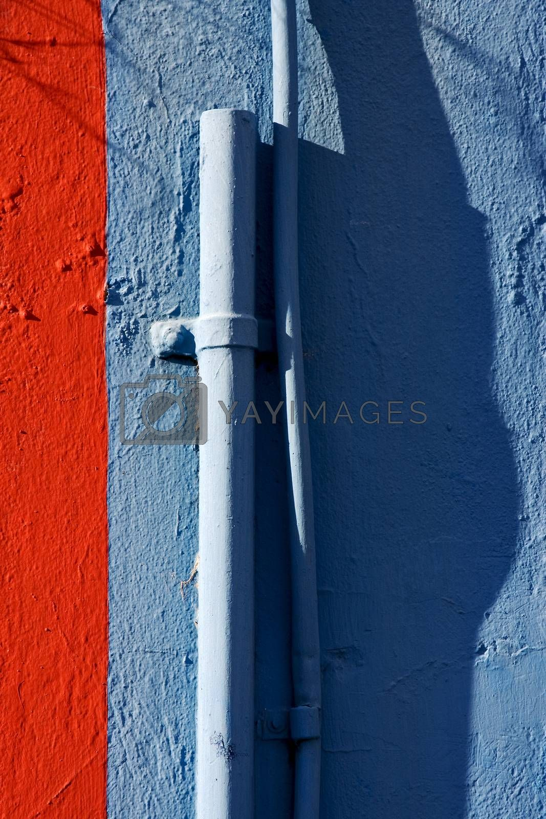 Royalty free image of blue colored pipe and red wall  by lkpro