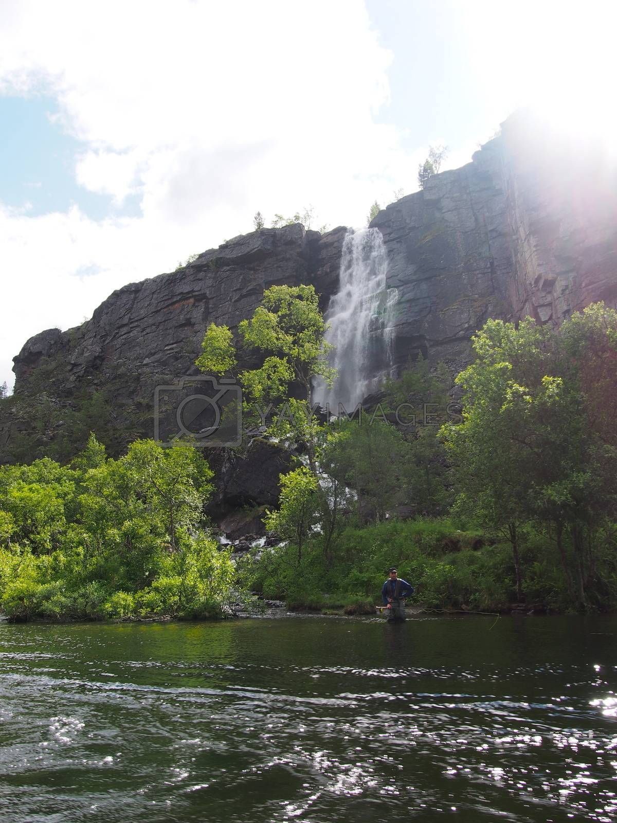 Flyfisher in front of waterfall, northern Norway