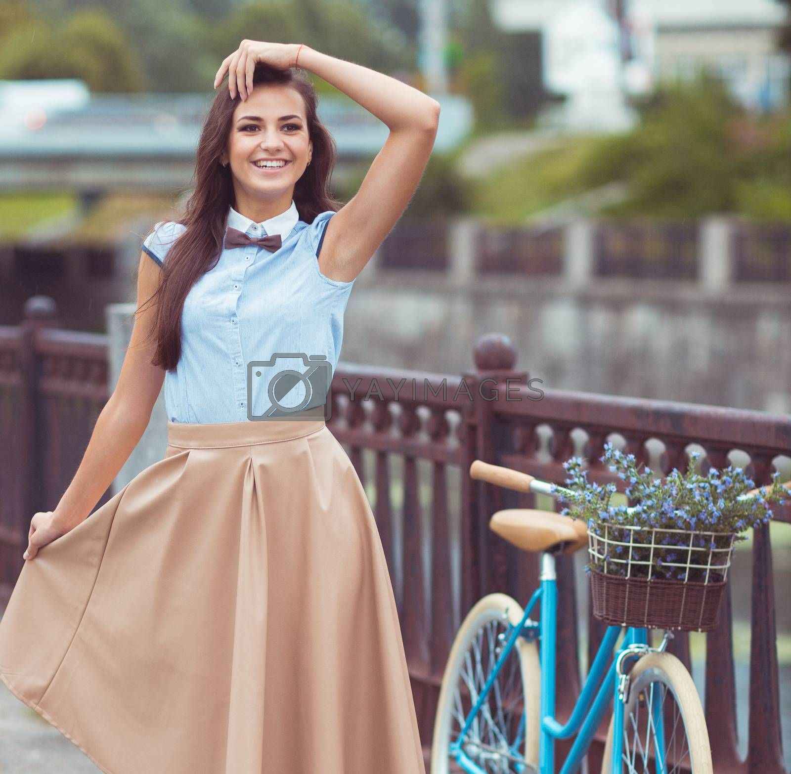 Royalty free image of Young beautiful, elegantly dressed woman with bicycle by vlad_star