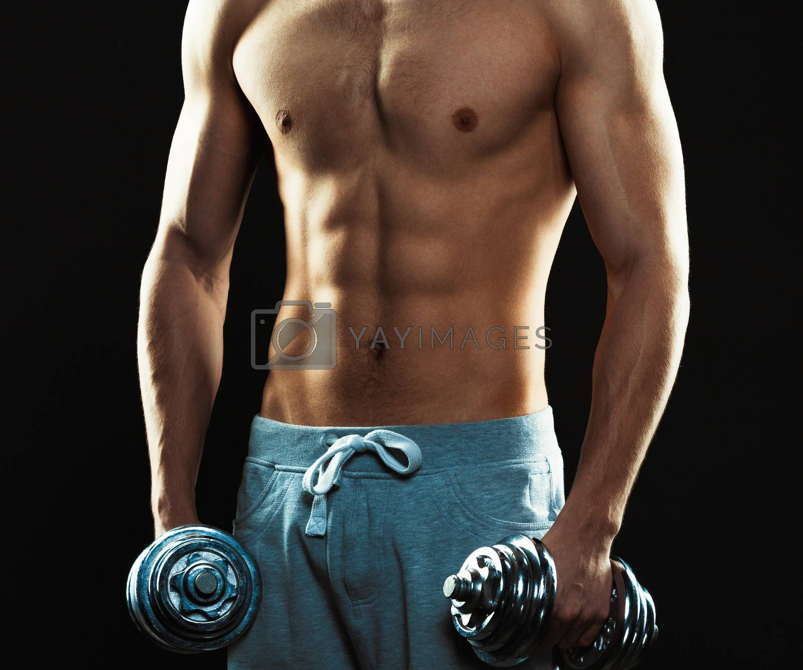 Royalty free image of Athletic man with dumbbells on the black background by vlad_star