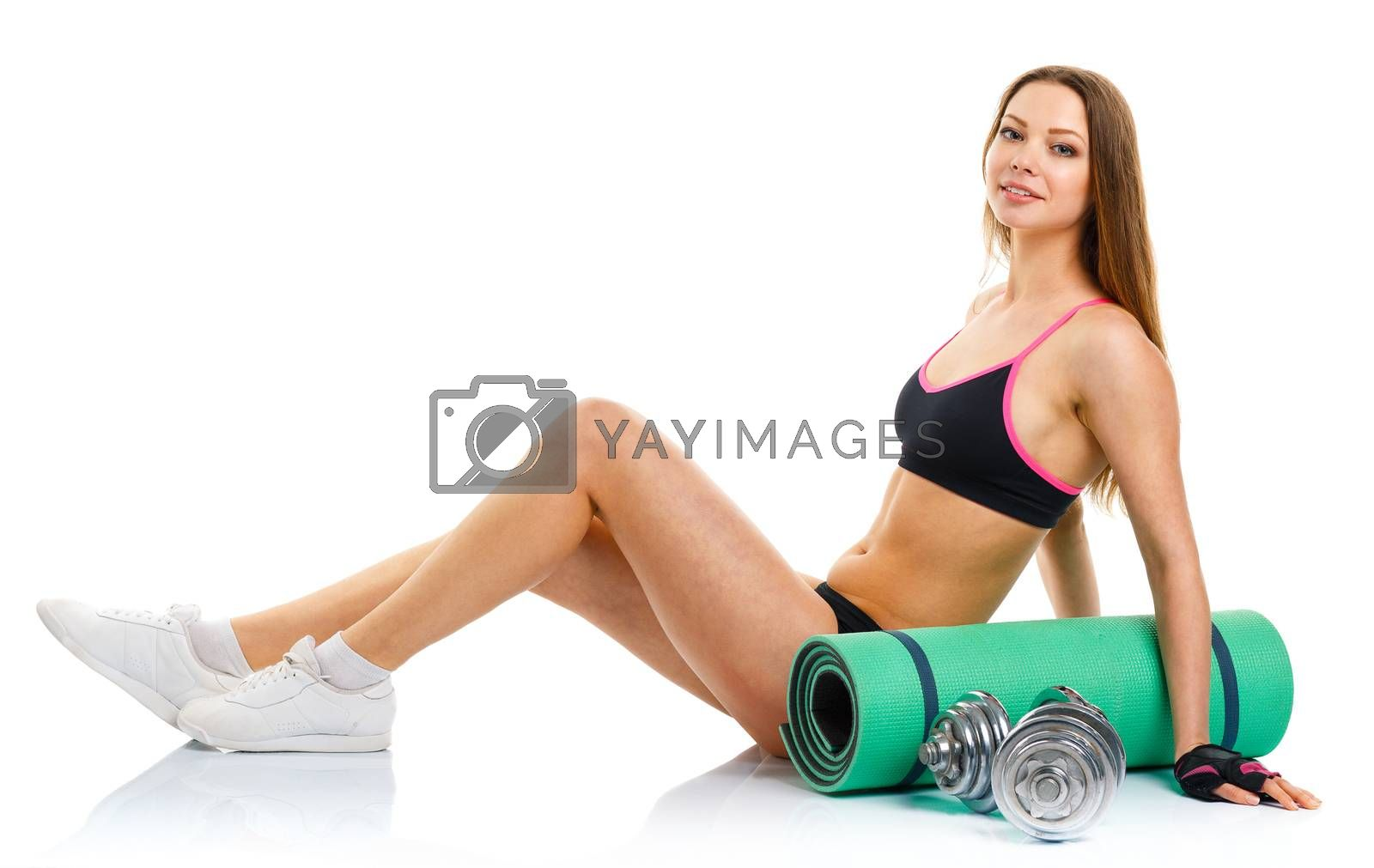 Royalty free image of Beautiful athletic woman with dumbbells, mat for fitness, a bott by vlad_star