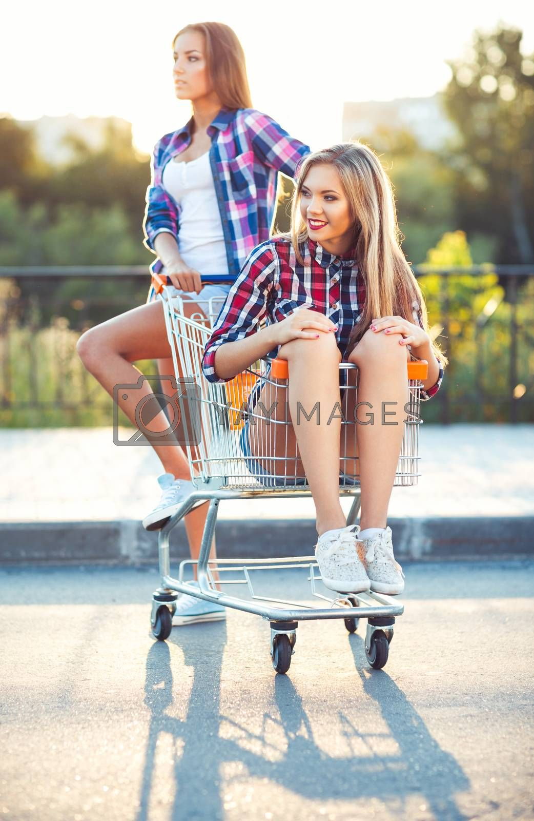 Royalty free image of Two happy beautiful teen girls driving shopping cart outdoors by vlad_star