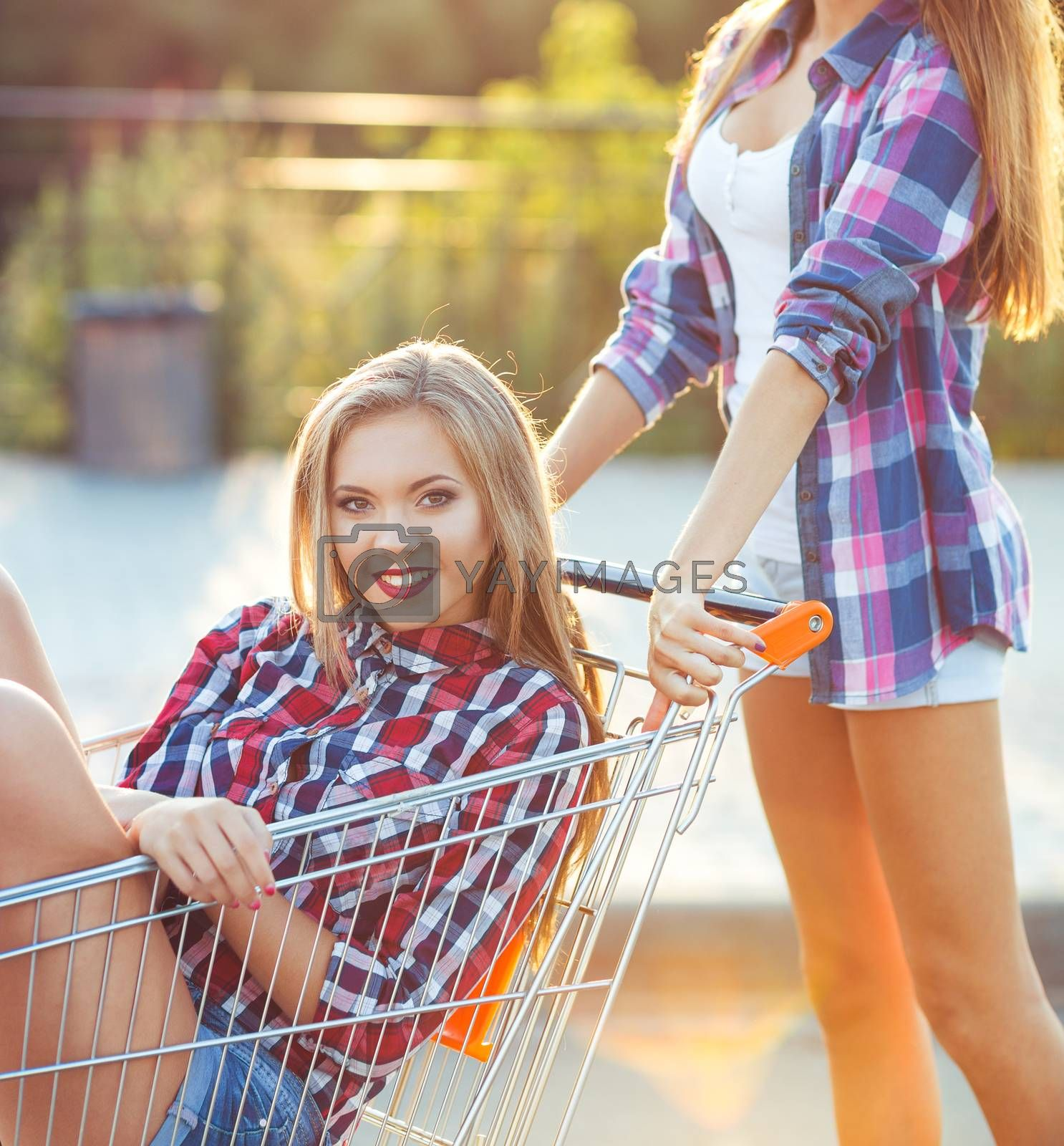 Two happy beautiful teen girls driving shopping cart outdoors by vlad_star