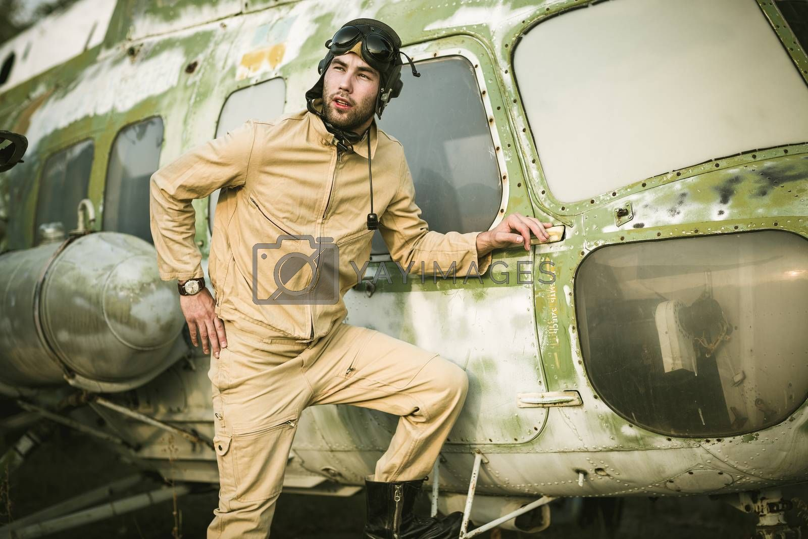 Young pilot posing near the helicopter by vlad_star