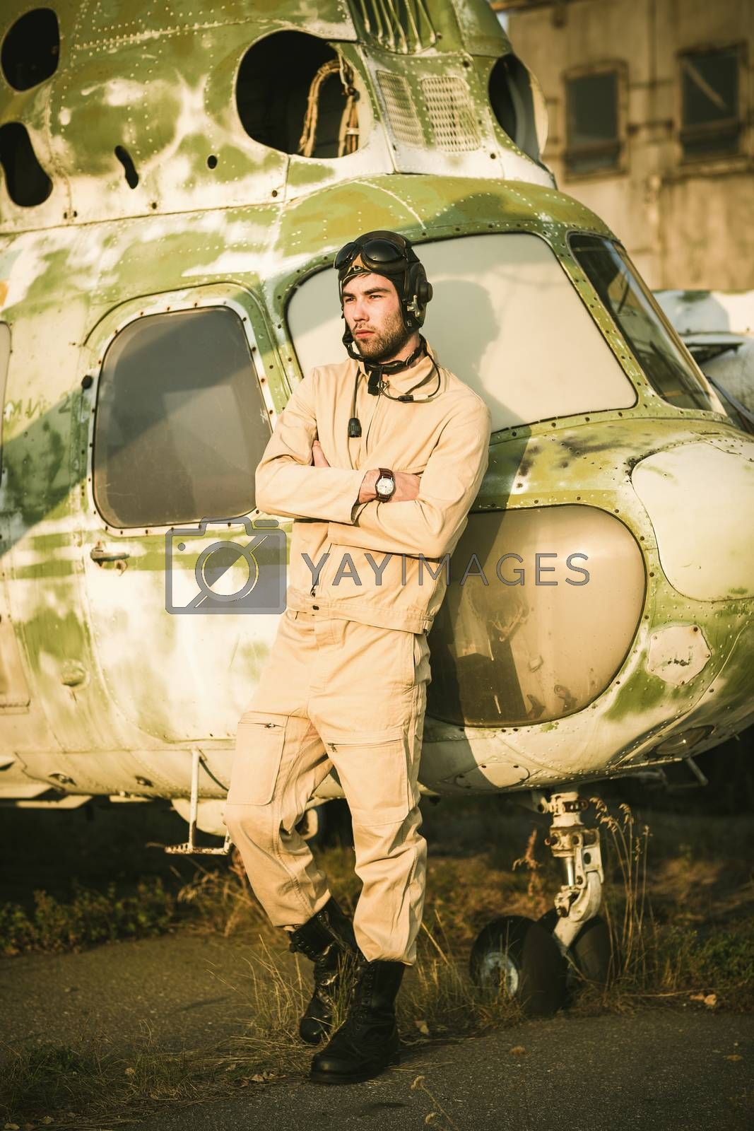 Royalty free image of Young pilot posing near the helicopter by vlad_star