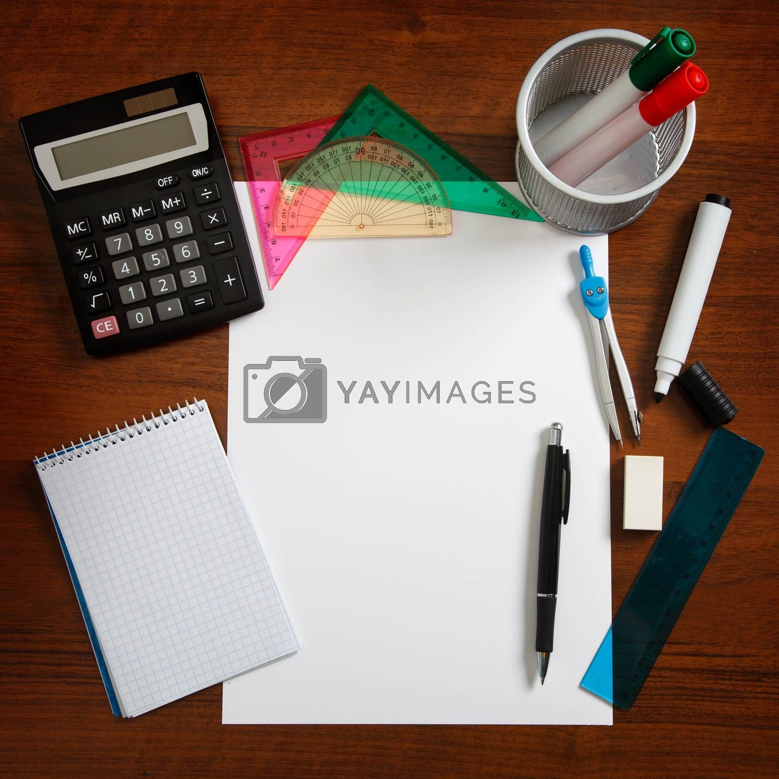 Desk with sheet of paper and stationery objects seen from above