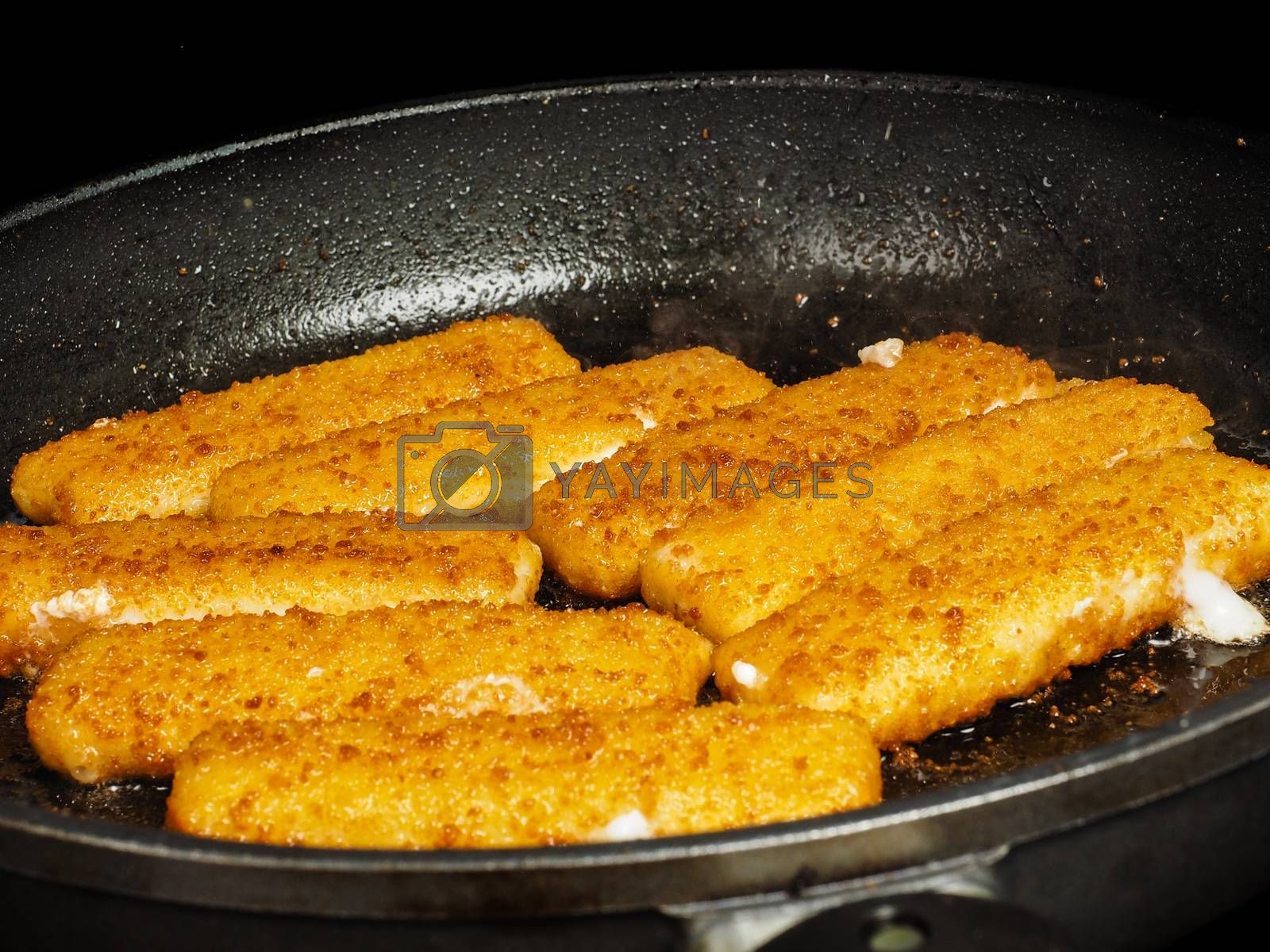 Closeup of crispy breaded fish fingers in hot fry pan by Arvebettum