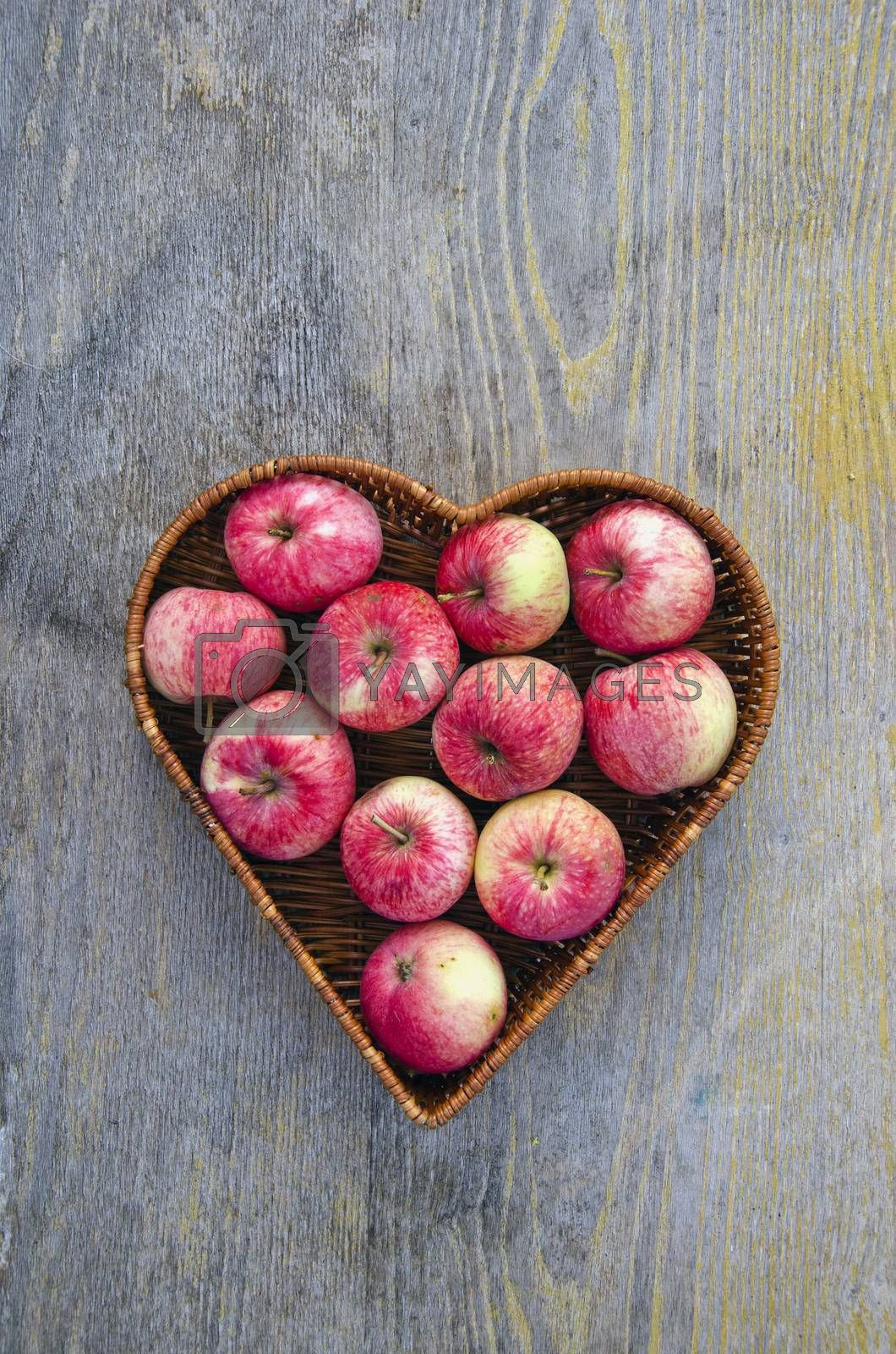 Royalty free image of red summer fresh apple in heart form basket by alis_photo
