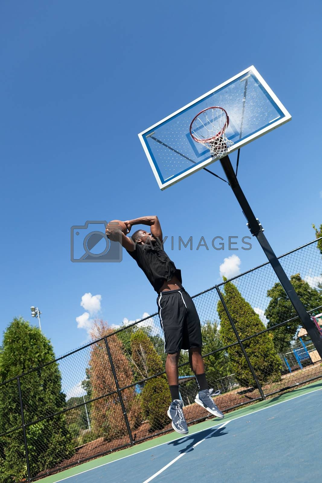 Young basketball player driving to the hoop for a high flying slam dunk. Shallow depth of field.