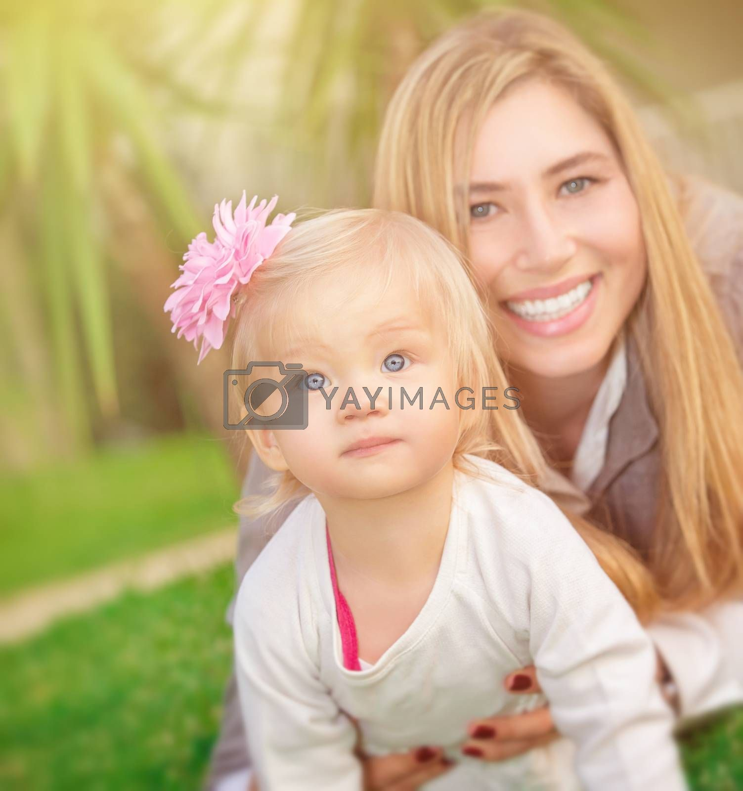 Mother with daughter playing outdoors, lying down on fresh green grass field in the park, happy family spending summer vacation