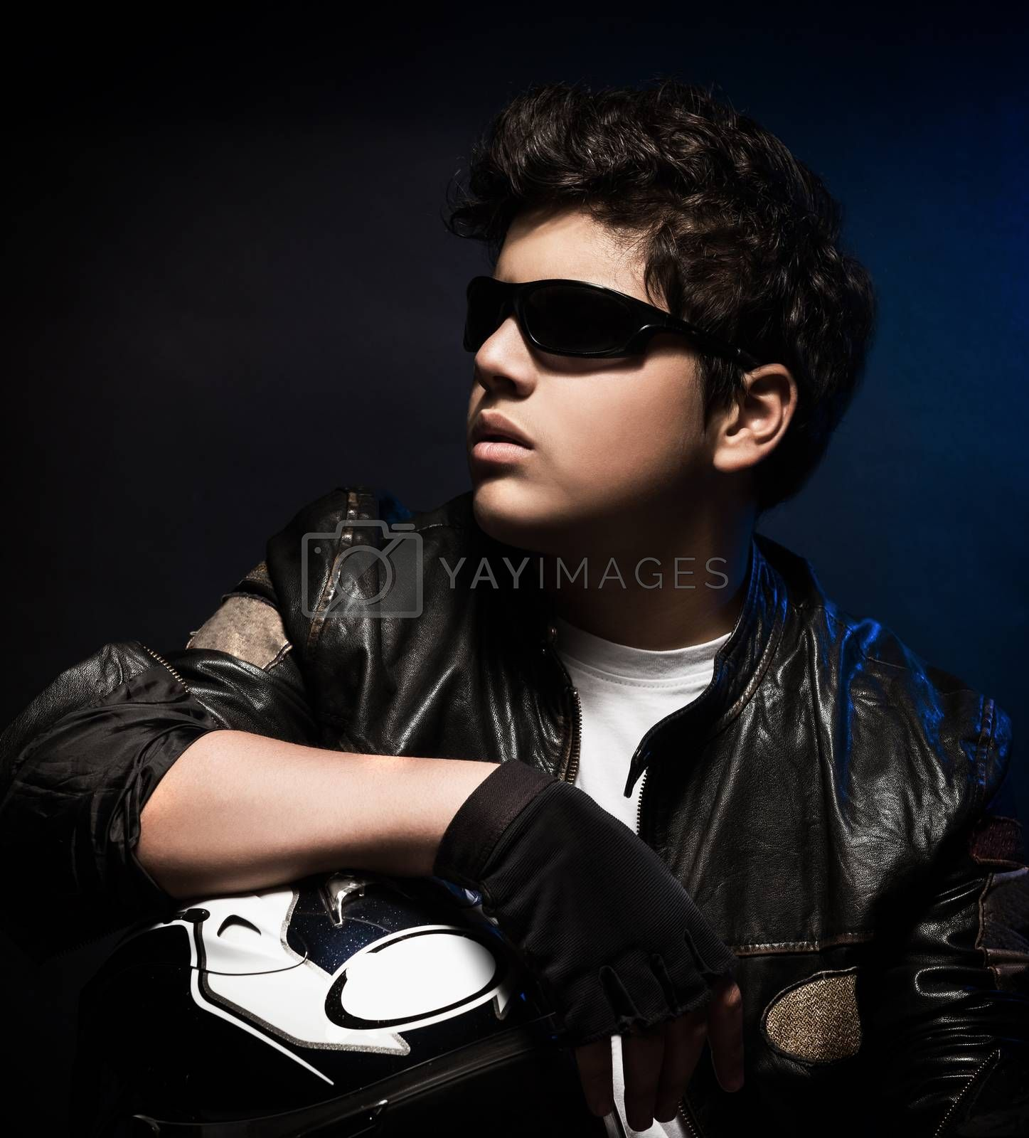 Portrait of handsome stylish biker over dark background, nice teen boy wearing fashion bikers outfit, enjoying extreme sport, active lifestyle
