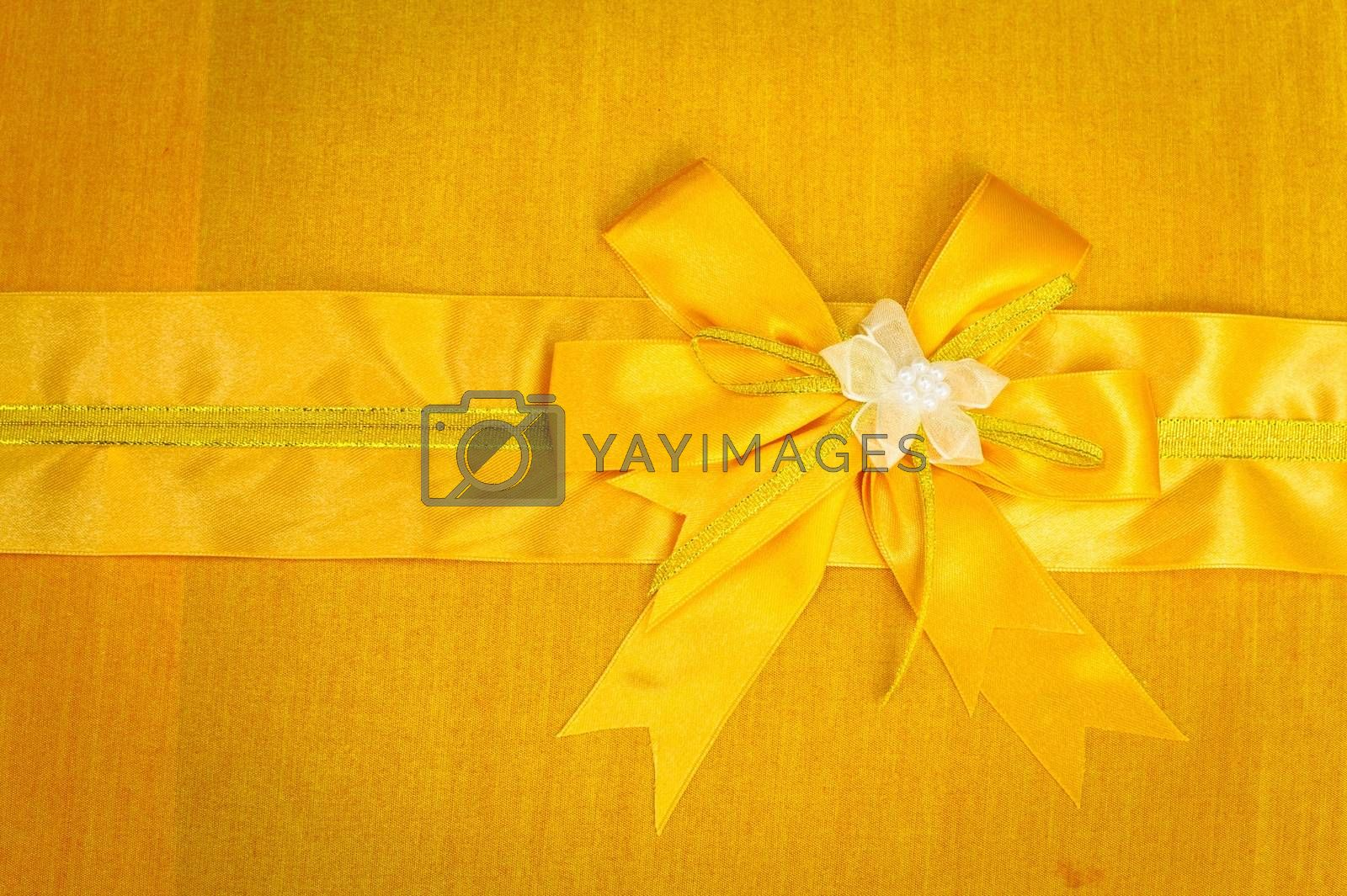 Abstract ribbon bow on fabric background.