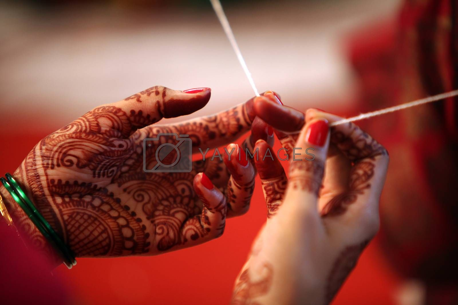 A religious thread held tight in the hands of a relative during a traditional hindu wedding ceremony.