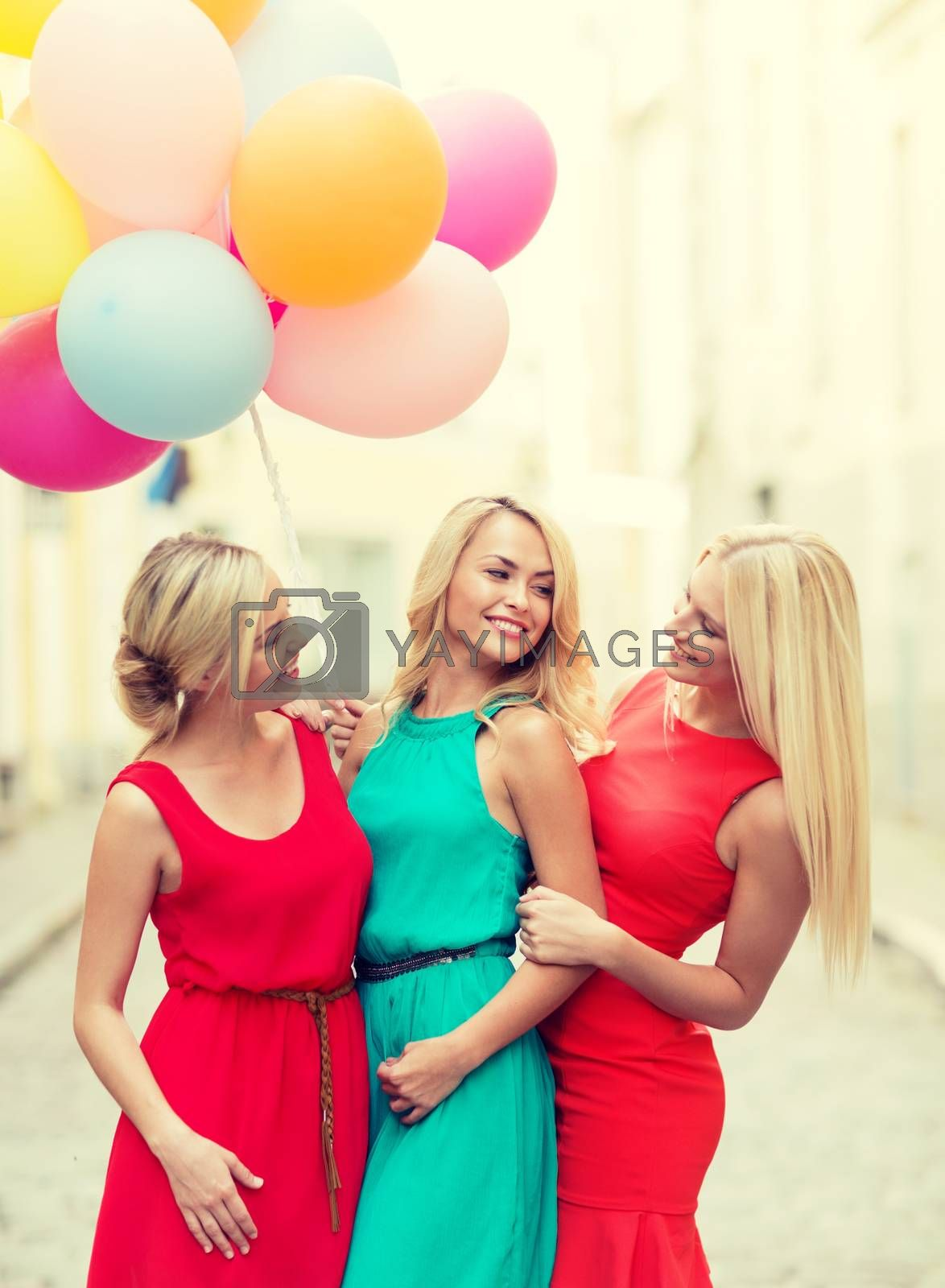 celebration and happy people concept - beautiful girls with colorful balloons in the city