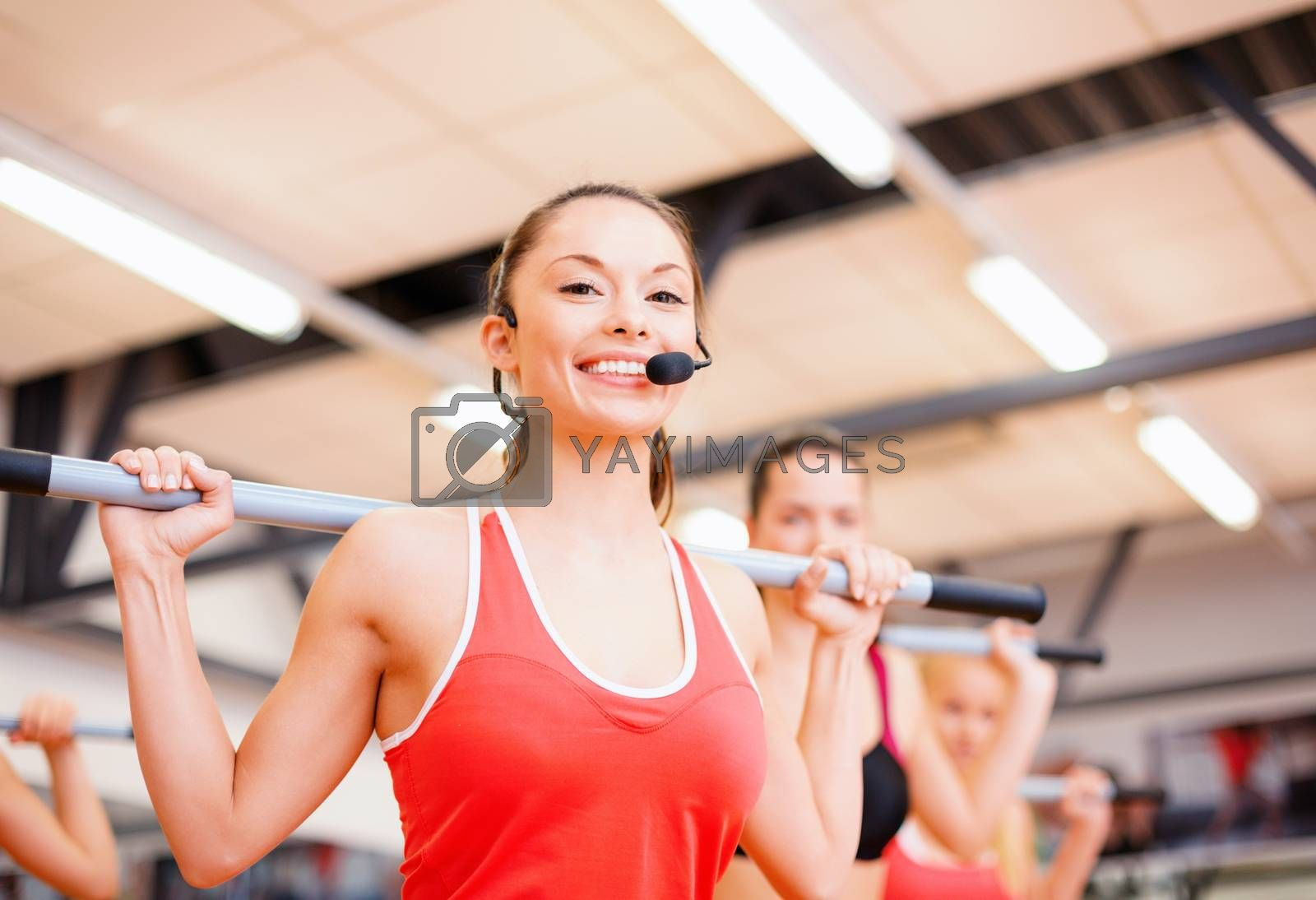 fitness, sport, training, gym and lifestyle concept - smiling trainer in front of the group of people working out with barbells in the gym