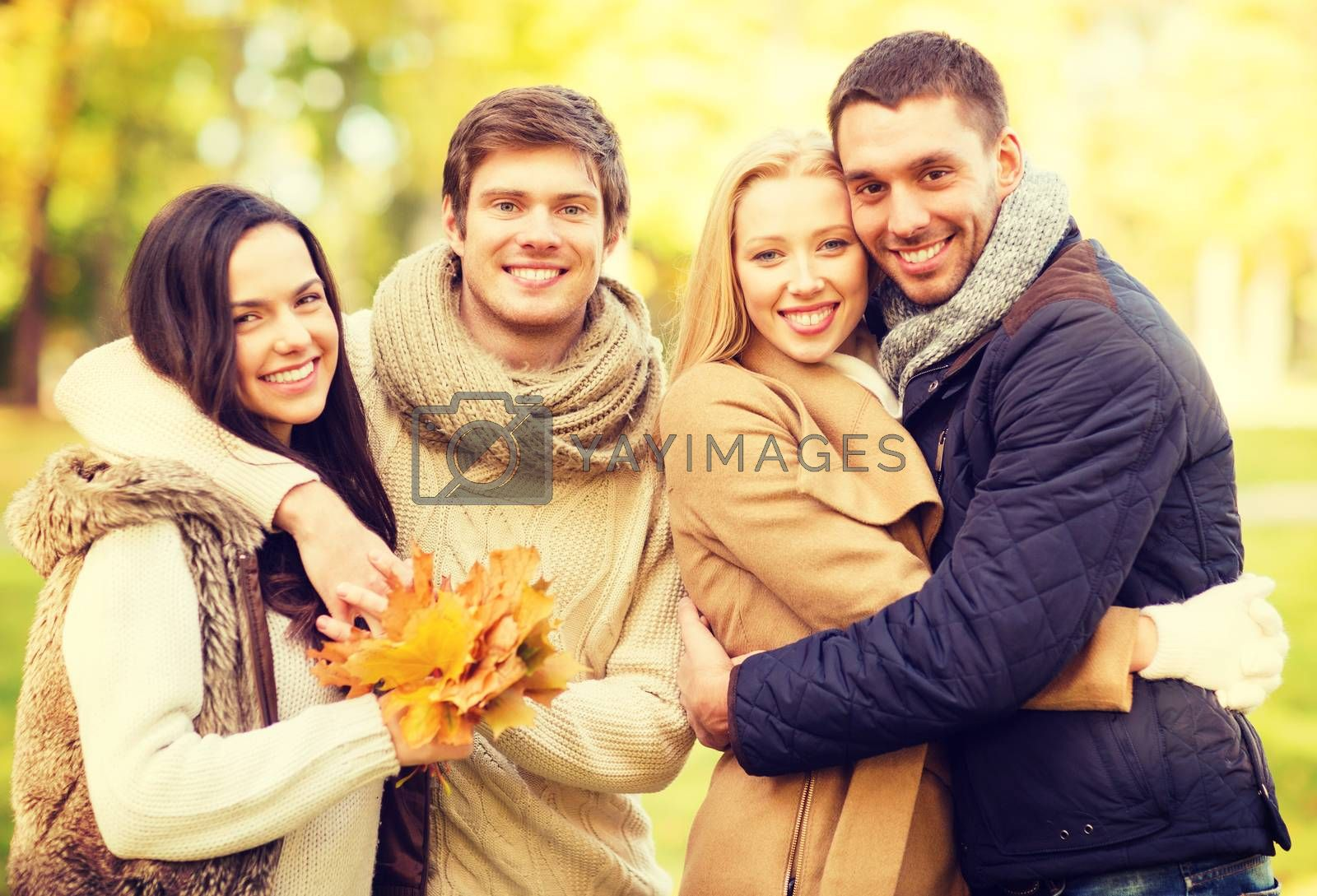 summer, holidays, vacation, happy people concept - group of friends or couples having fun in autumn park