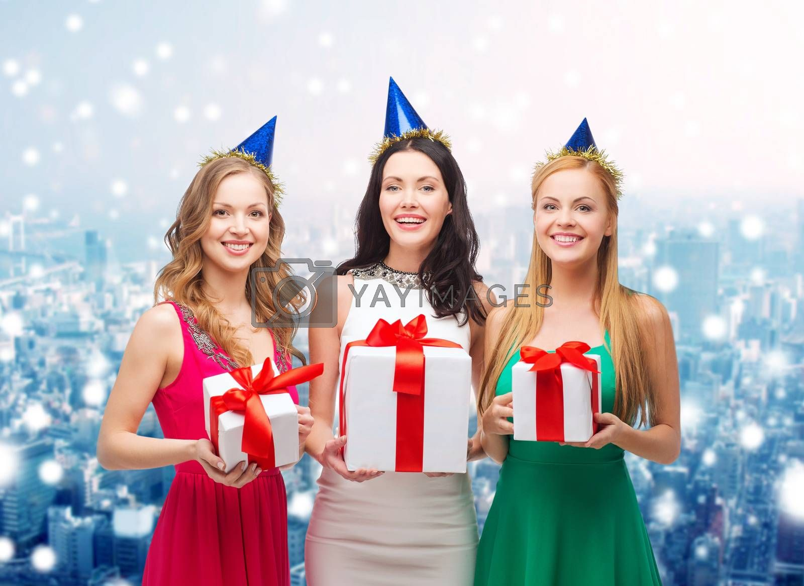 presents, holidays, people and celebration concept - smiling women in party caps with gift boxes over snowy city background