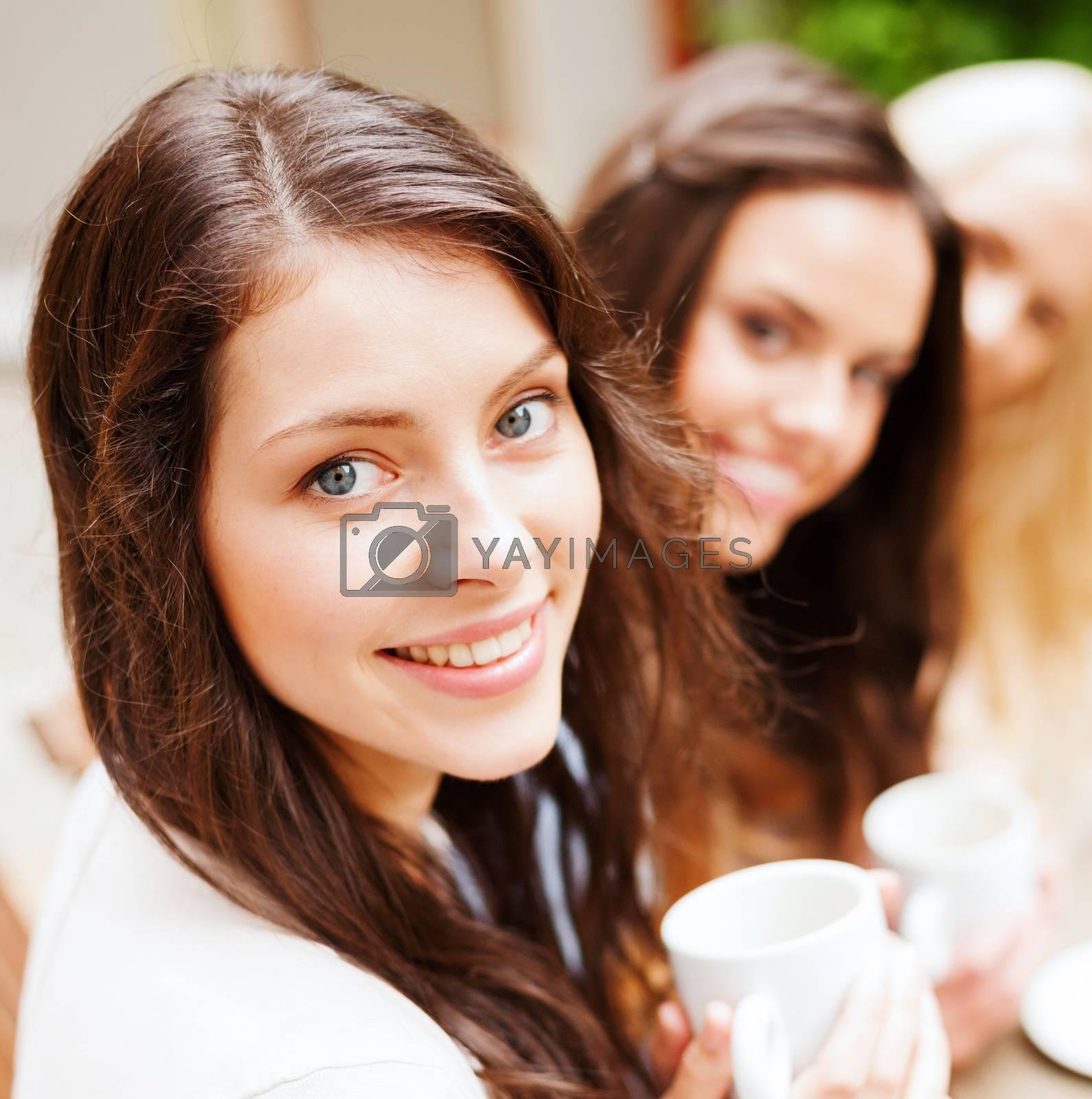 beautiful girls drinking coffee in cafe by dolgachov
