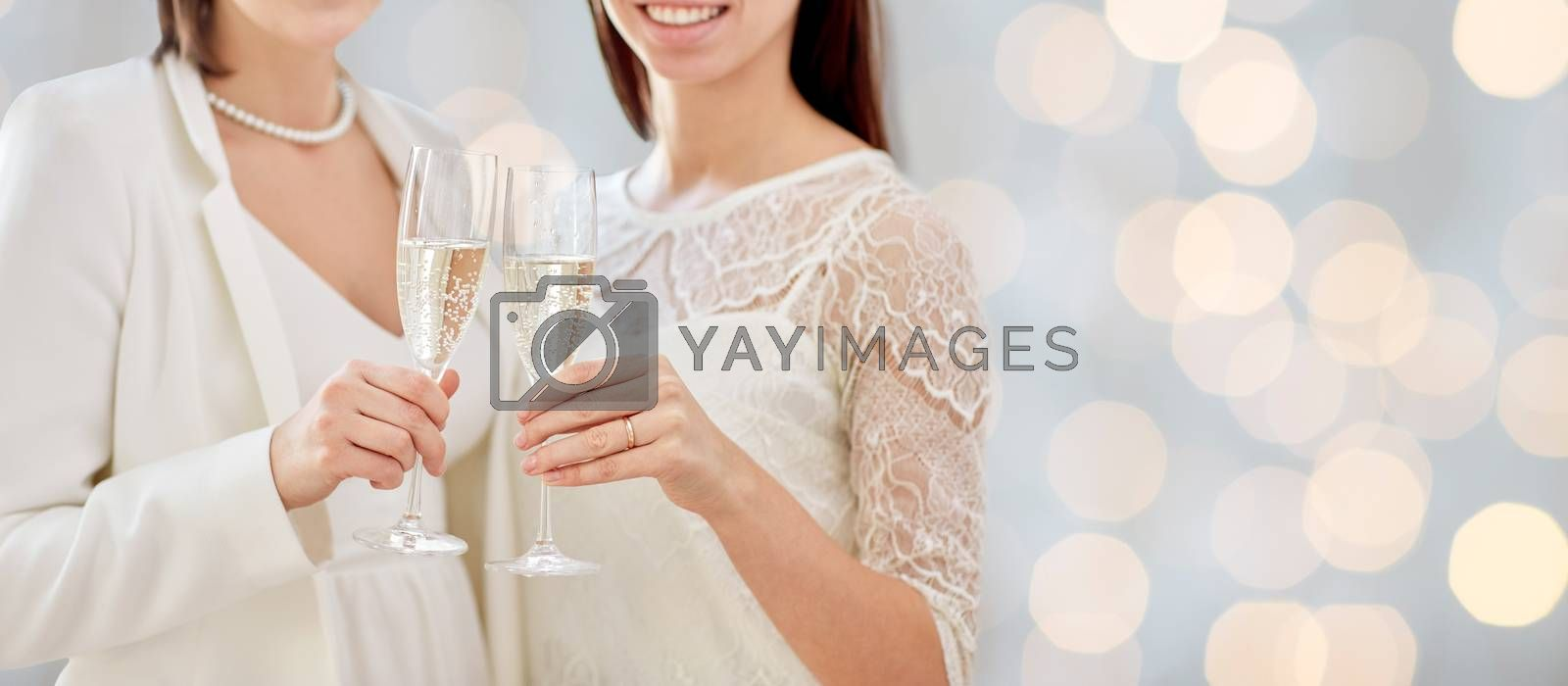 people, homosexuality, same-sex marriage, celebration and love concept - close up of happy married lesbian couple holding and clinking champagne glasses over holidays lights background