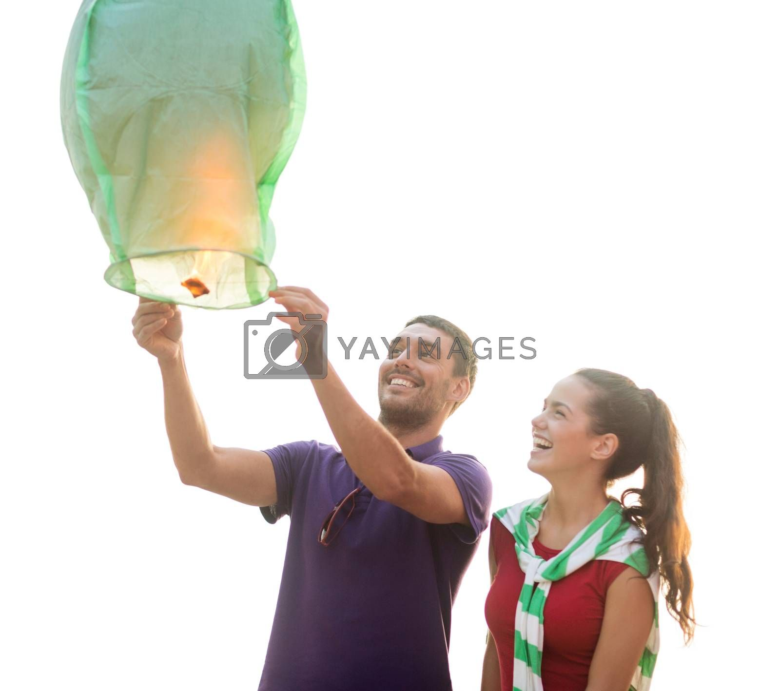 summer holidays, vacation, celebration and people concept - group happy couple with chinese sky lantern on beach
