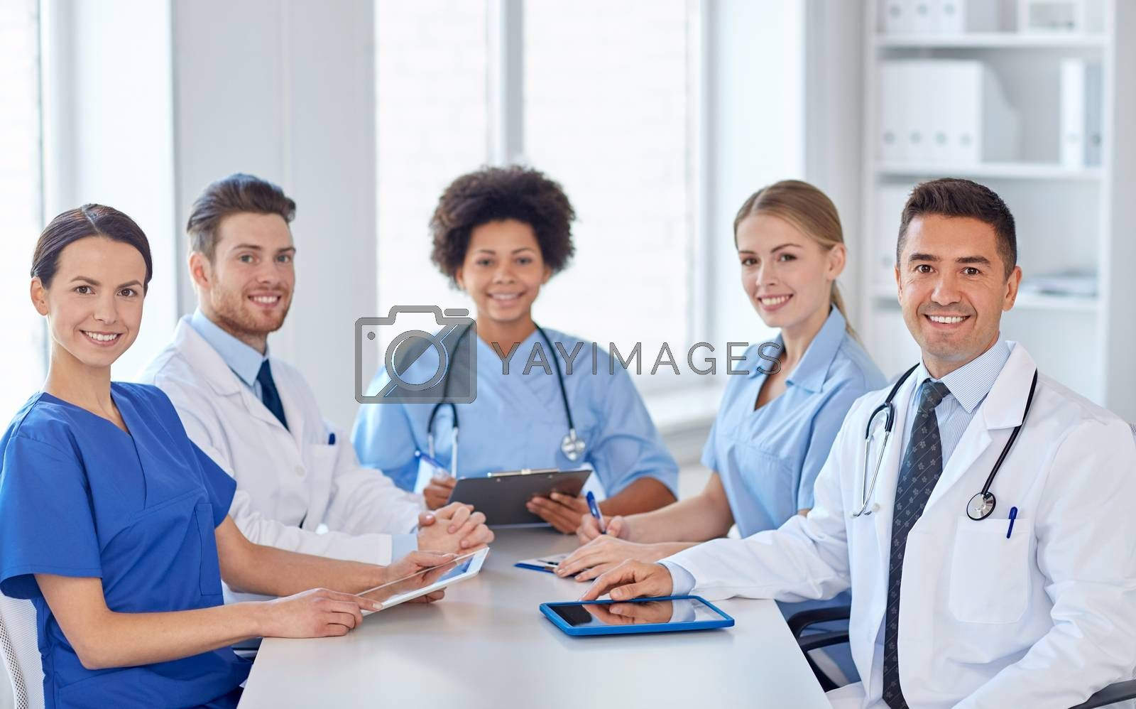 hospital, profession, people and medicine concept - group of happy doctors meeting at medical office
