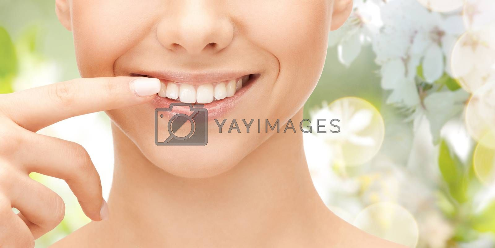 dental health, beauty, hygiene and people concept - close up of smiling woman face pointing to teeth over green natural background