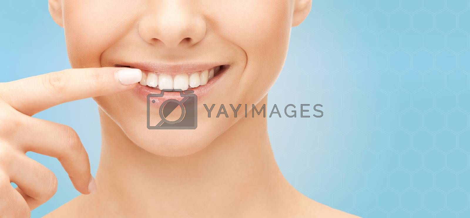 close up of smiling woman face pointing to teeth by dolgachov
