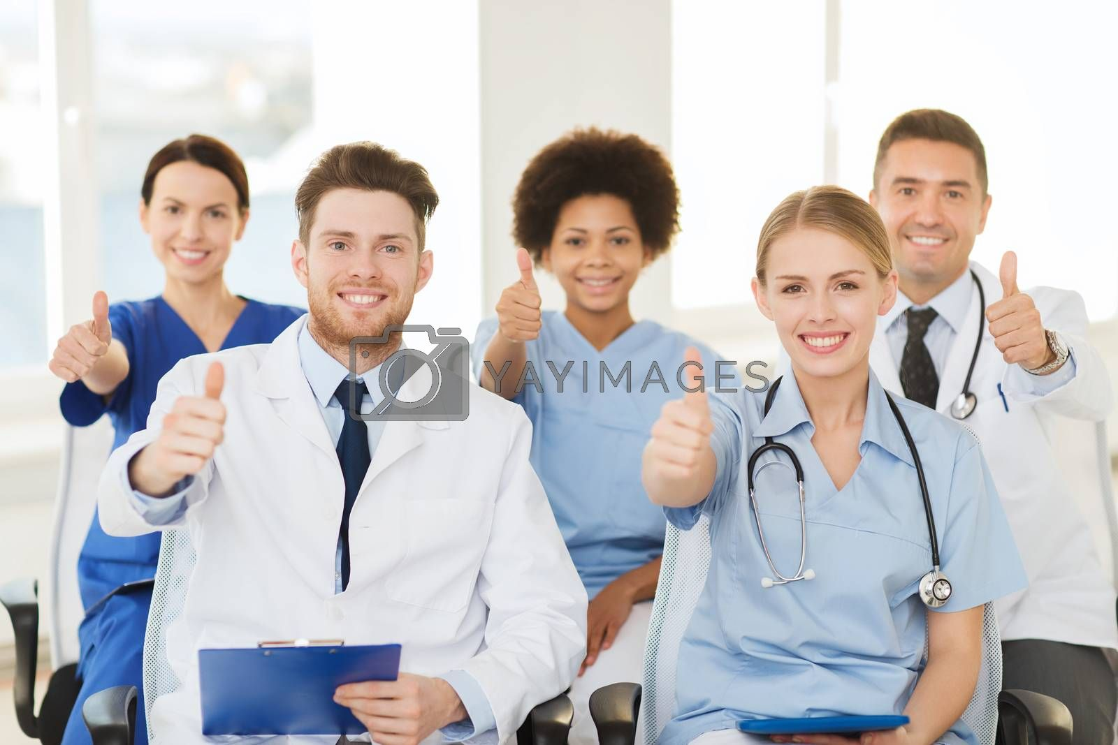 hospital, profession, people and medicine concept - group of happy doctors on seminar in lecture hall at hospital showing thumbs up gesture