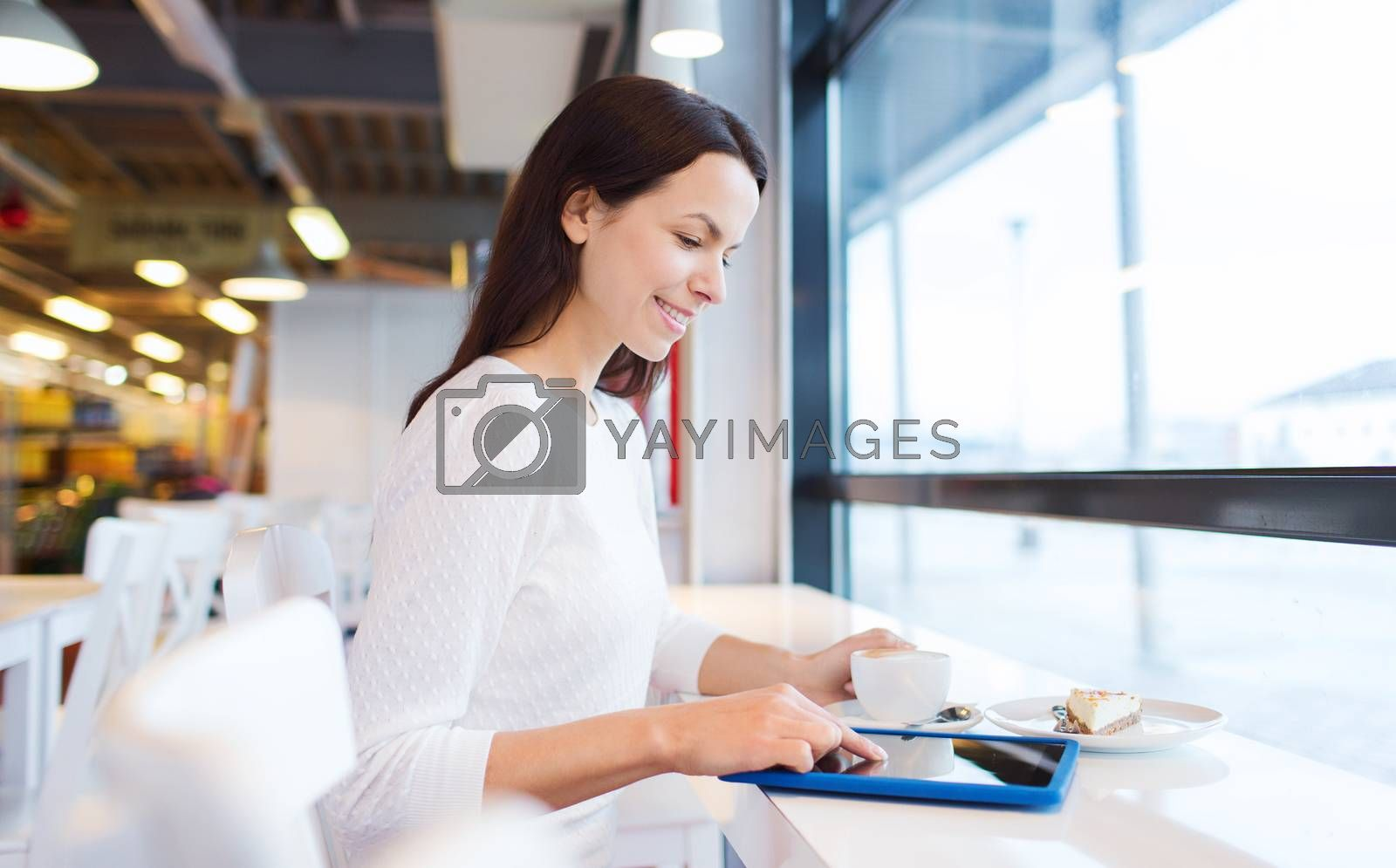 leisure, drinks, people, technology and lifestyle concept - smiling young woman with tablet pc computer drinking coffee at cafe