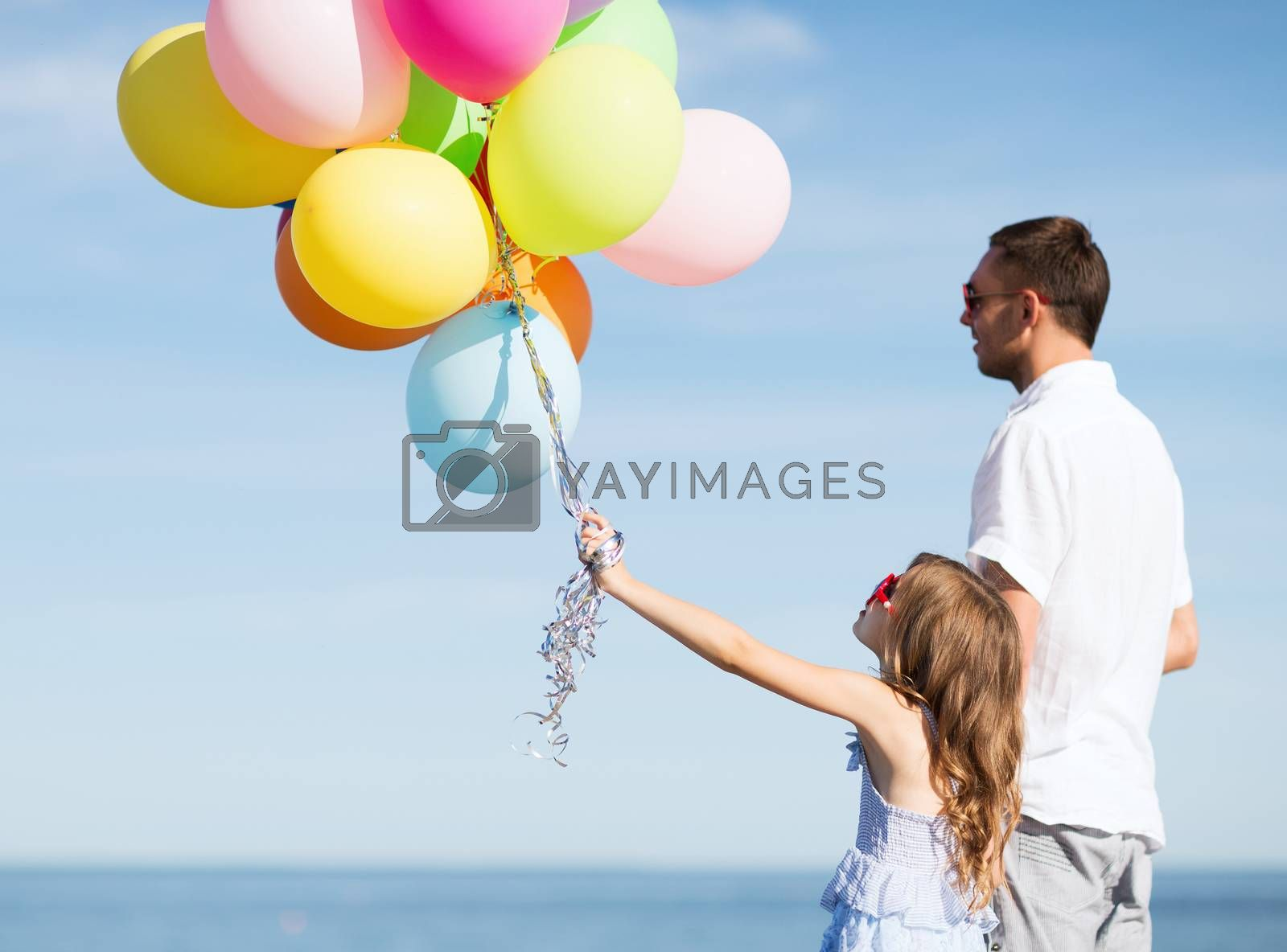 summer holidays, celebration, children and family concept - father and daughter with colorful balloons