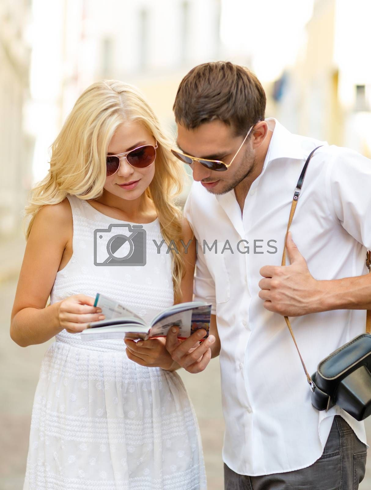 summer holidays, dating, city break and tourism concept - couple with map, camera and travellers guide