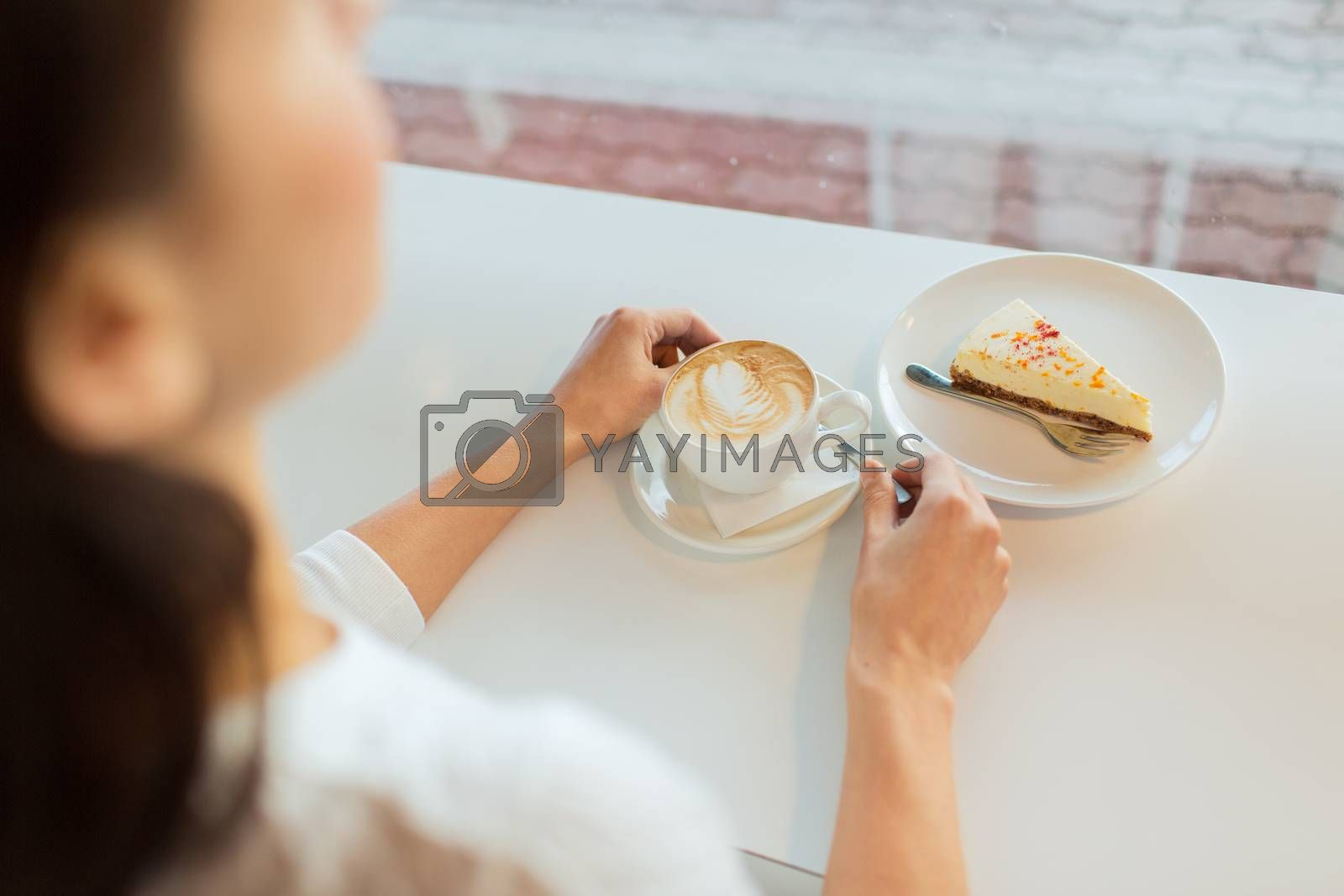 leisure, food and drinks, people and lifestyle concept - close up of young woman hands eating cake and drinking coffee at cafe