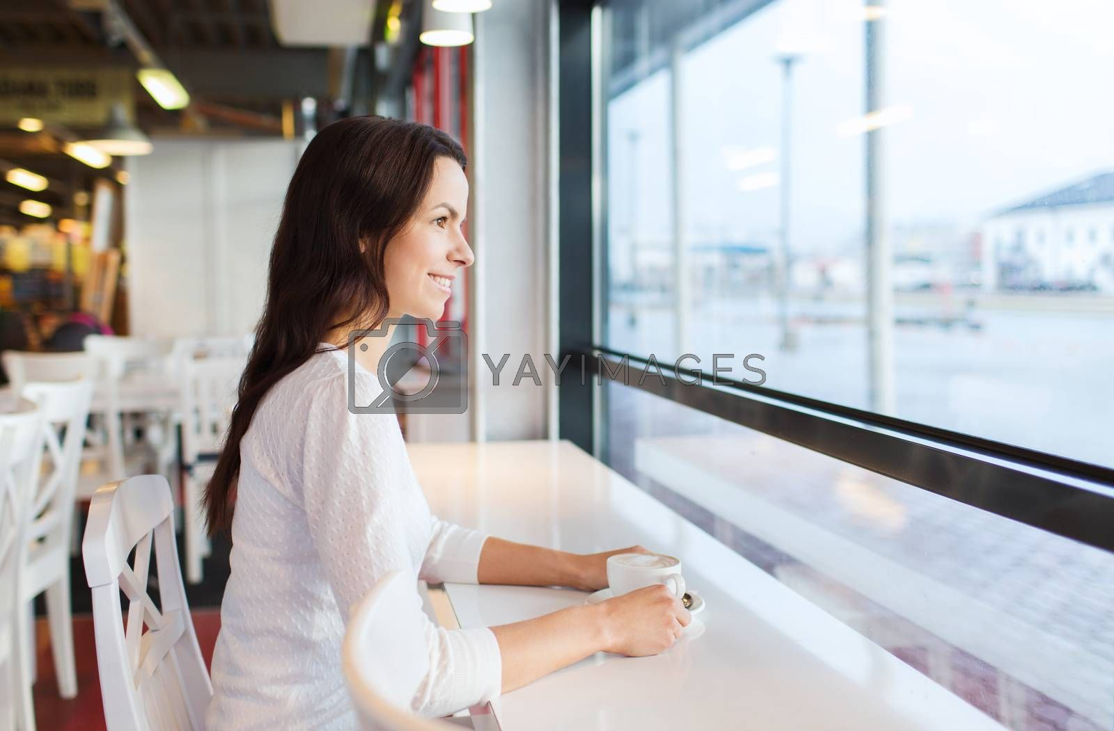 leisure, drinks, people and lifestyle concept - smiling young woman drinking coffee at cafe