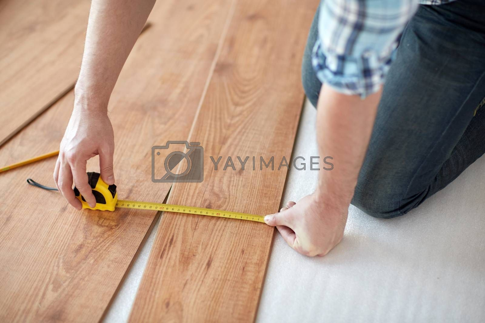repair, building, floor and people concept - close up of male  hands measuring wooden flooring with ruler and making mark by pencil