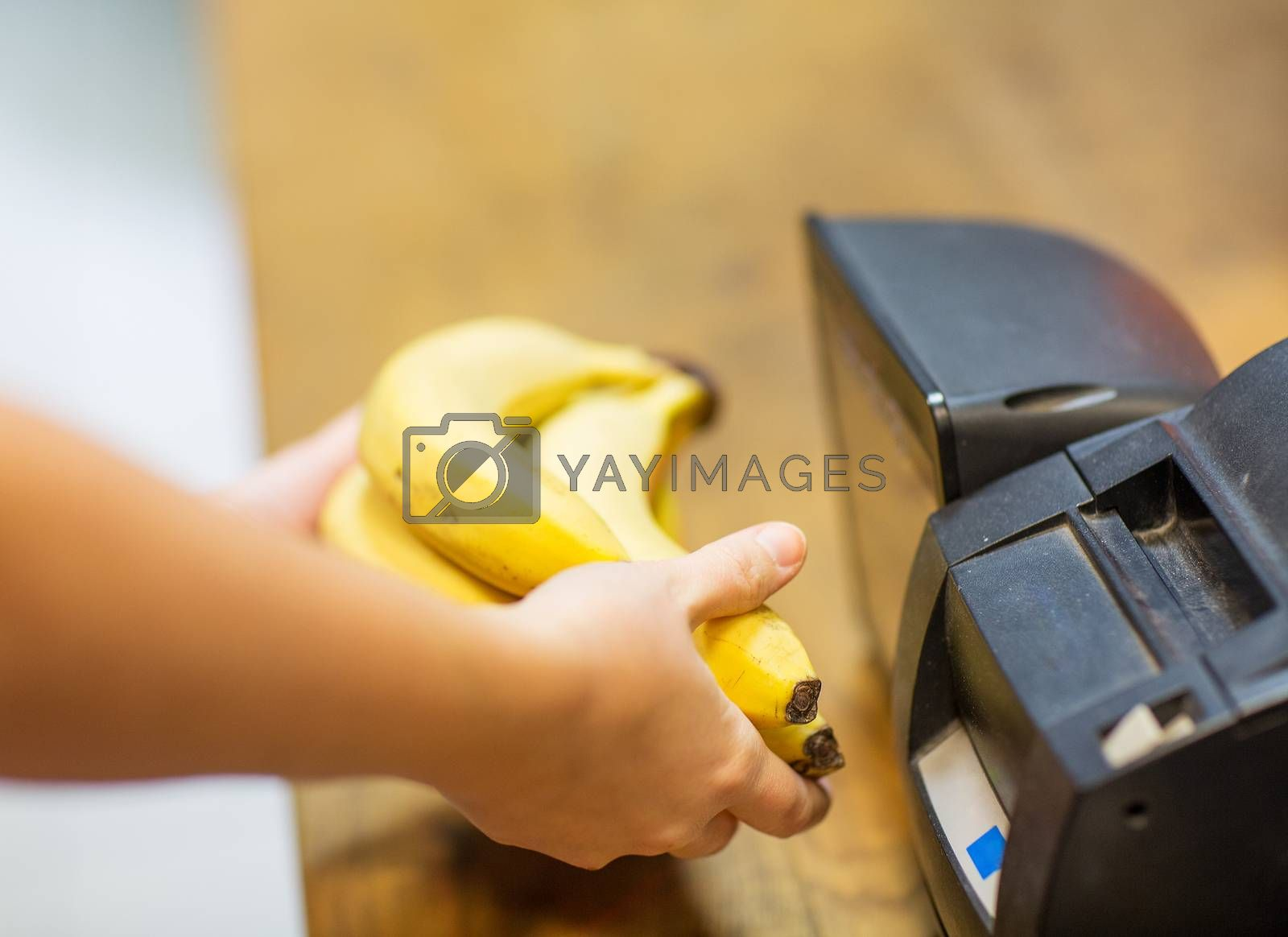 sale, shopping, payment, consumerism and people concept - close up of hands buying or scanning bananas at checkout in food market or mall