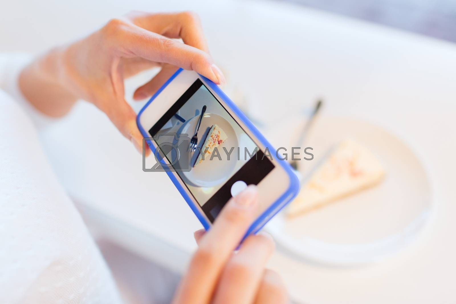 food, people, technology and lifestyle concept - close up of woman hands with smartphone taking cake picture at cafe