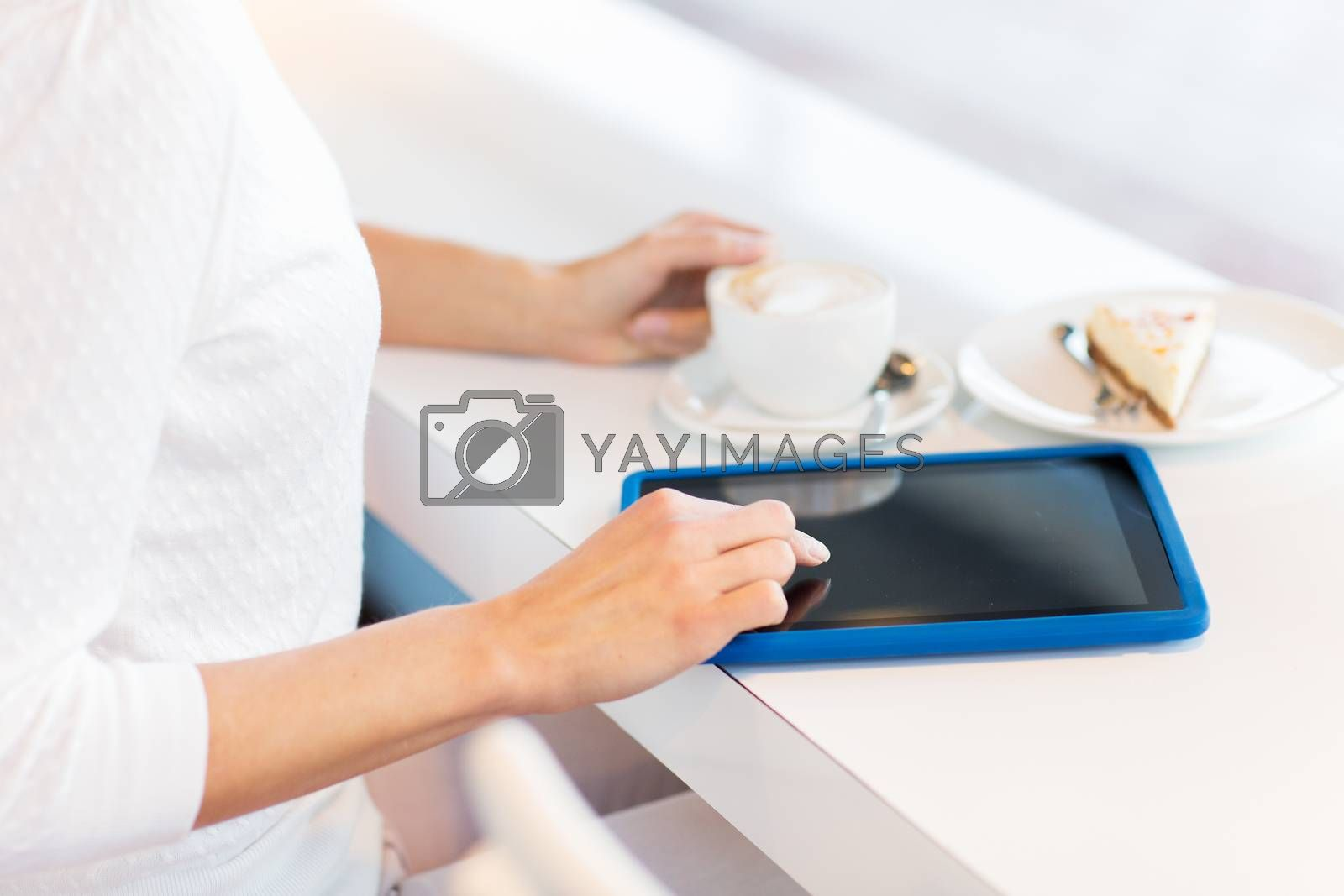 leisure, people, technology and lifestyle concept - close up of young woman hands with tablet pc computer drinking coffee and eating cake at cafe