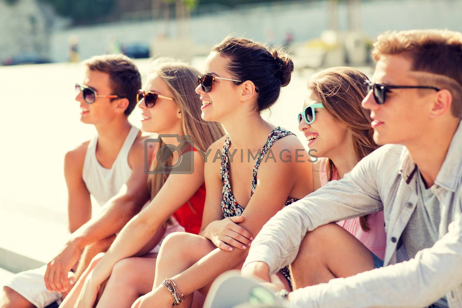 friendship, leisure, summer and people concept - group of smiling friends sitting on city square