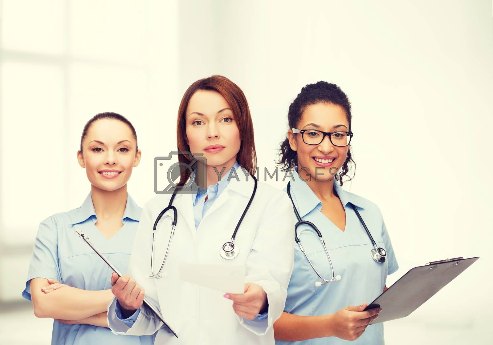 healthcare and medicine concept - calm female doctor and nurses with clipboard and stethoscope giving prescription